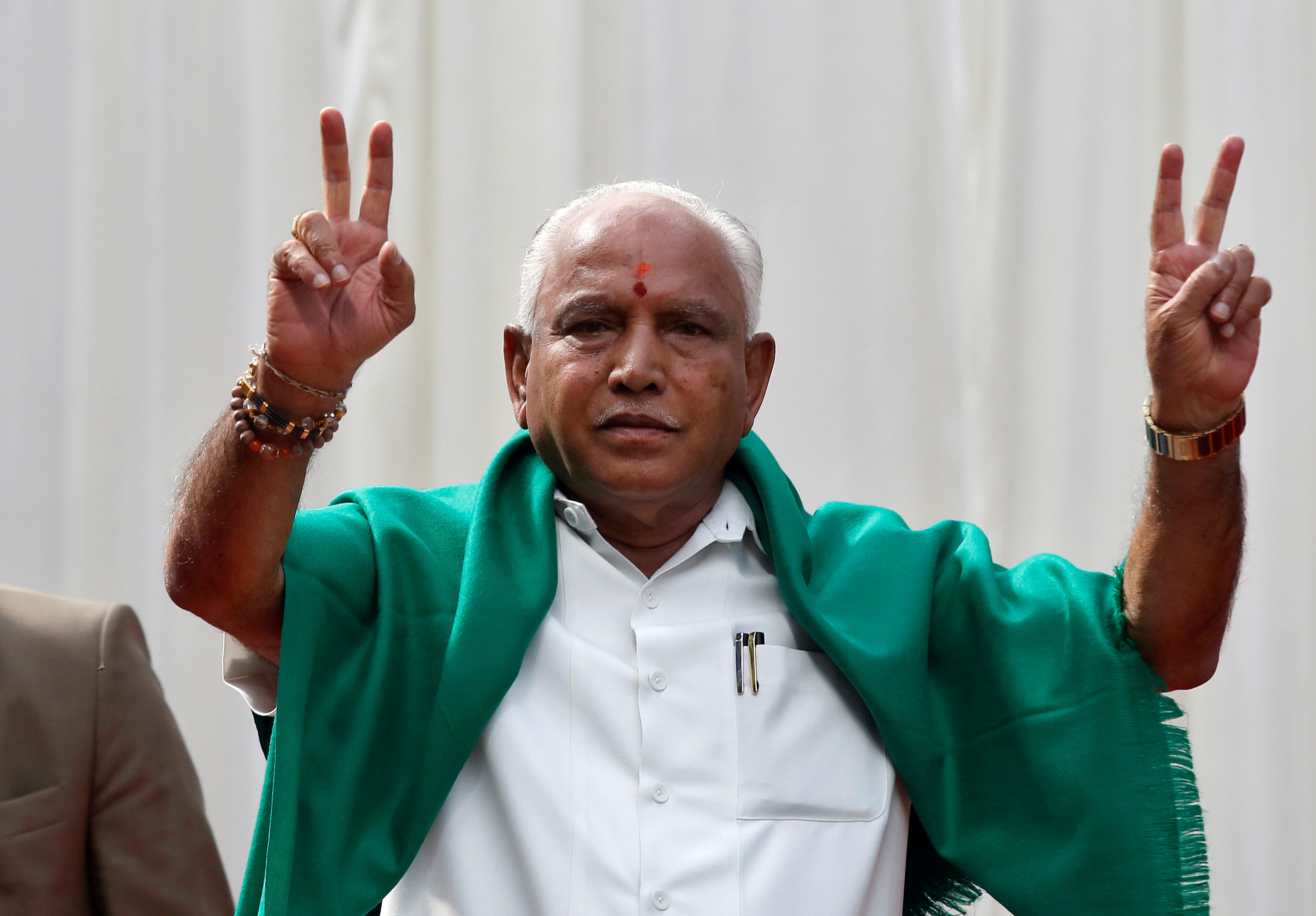 India's ruling Bharatiya Janata Party (BJP) leader B. S. Yeddyurappa flashes the victory sign after taking oath as Chief Minister of the southern state of Karnataka inside the governor's house in Bengaluru, India, May 17, 2018. REUTERS/Abhishek N. Chinnappa/File Photo