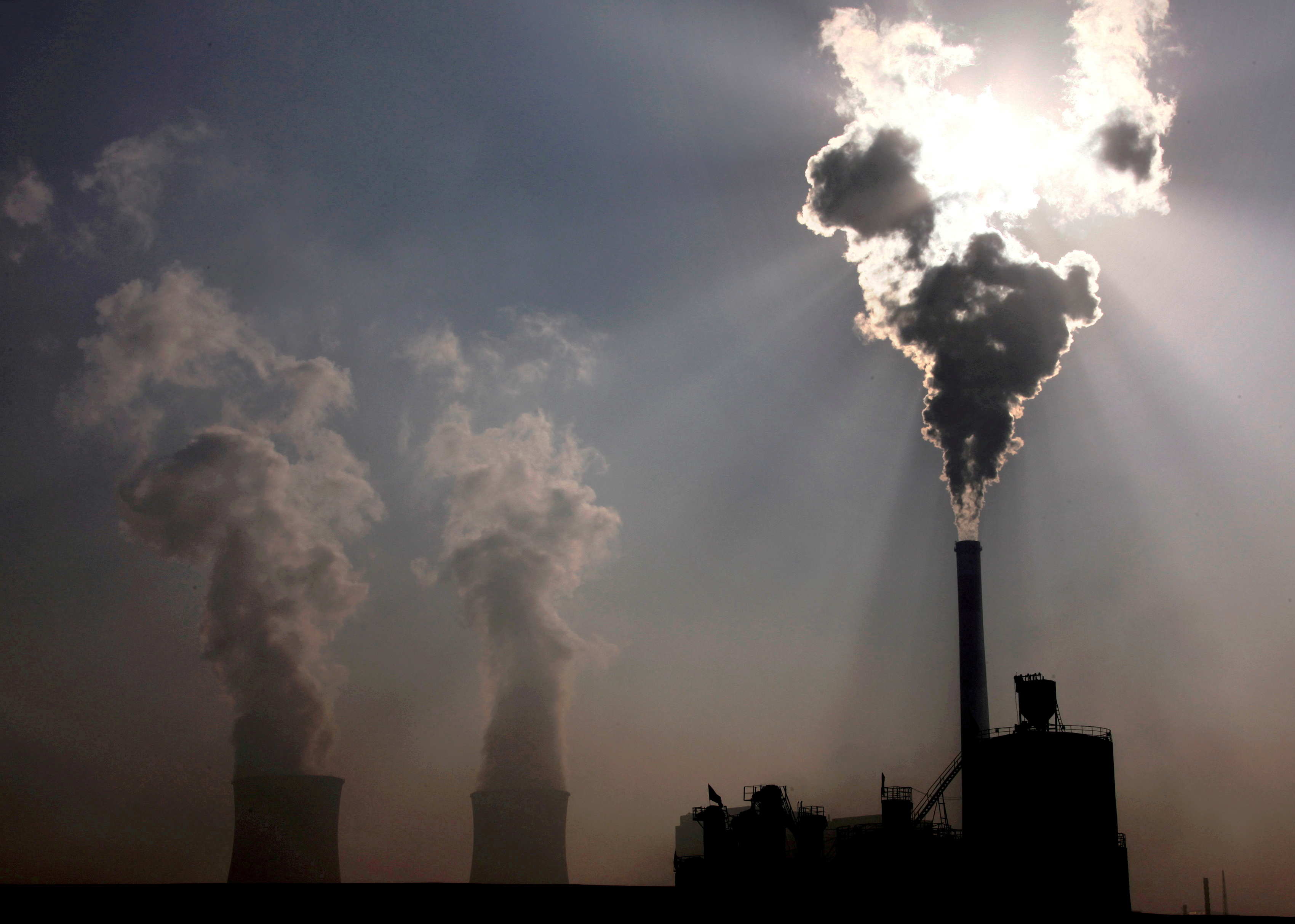 A coal-burning power plant can be seen behind a factory in the city of Baotou, in China's Inner Mongolia Autonomous Region, October 31, 2010.  REUTERS/David Gray/File Photo - RC2SYP9ETGNL