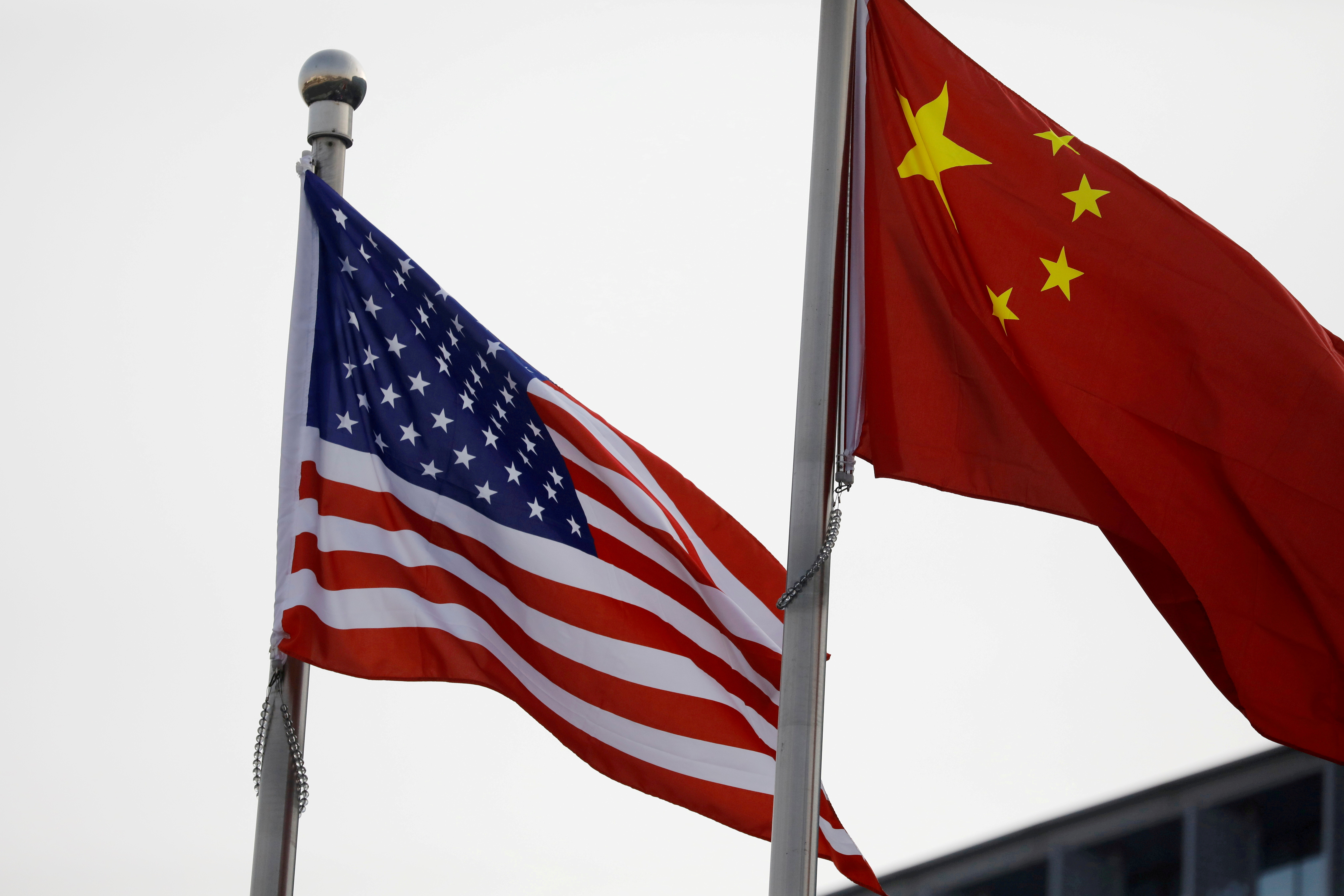 Chinese and U.S. flags flutter outside the building of an American company in Beijing, China January 21, 2021. REUTERS/Tingshu Wang/File Photo