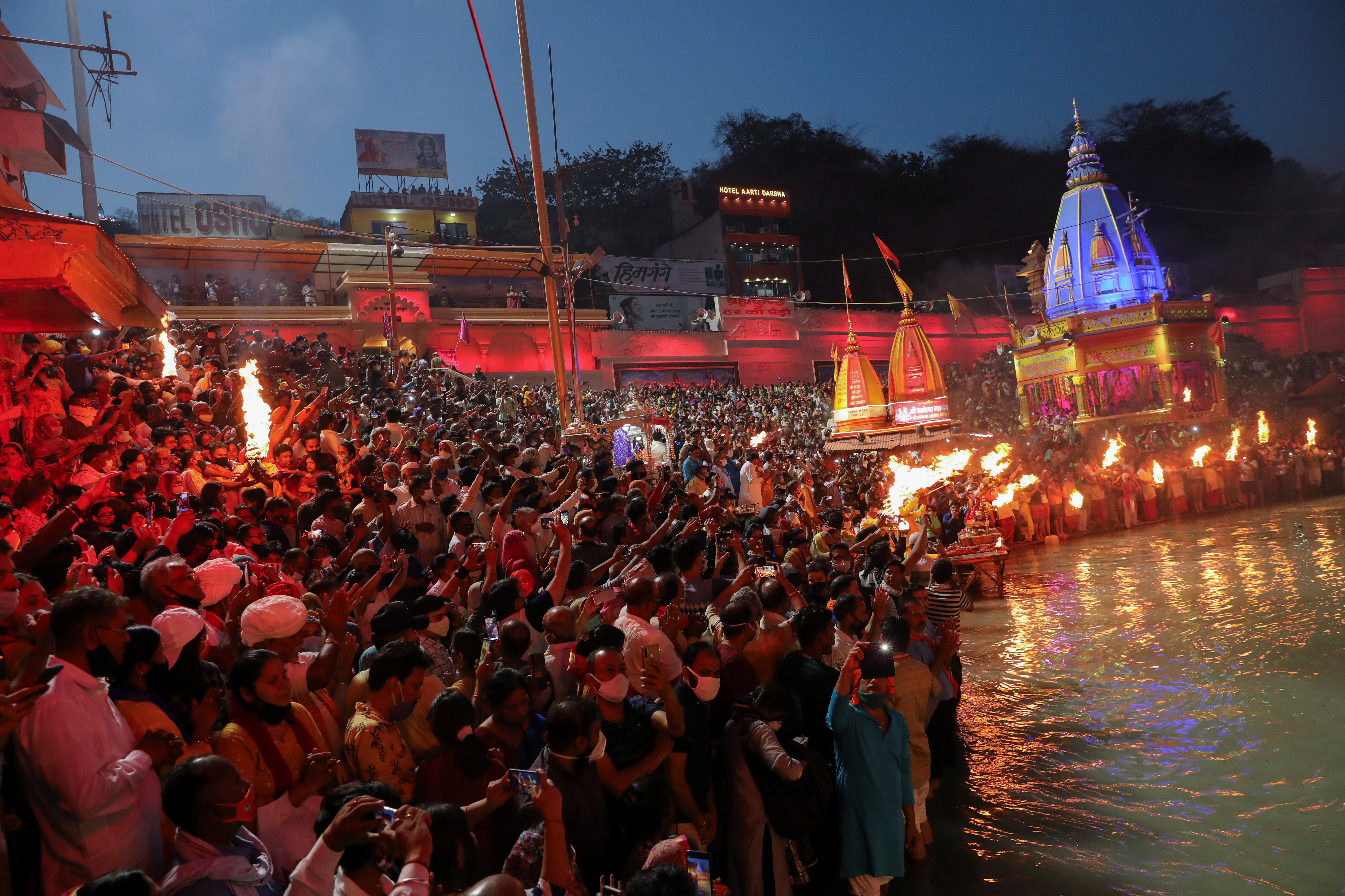 Devotees gather for an evening prayer on the banks of Ganges river during Kumbh Mela, or the Pitcher Festival, amidst the spread of the coronavirus disease (COVID-19), in Haridwar, India, April 11, 2021. REUTERS/Anushree Fadnavis