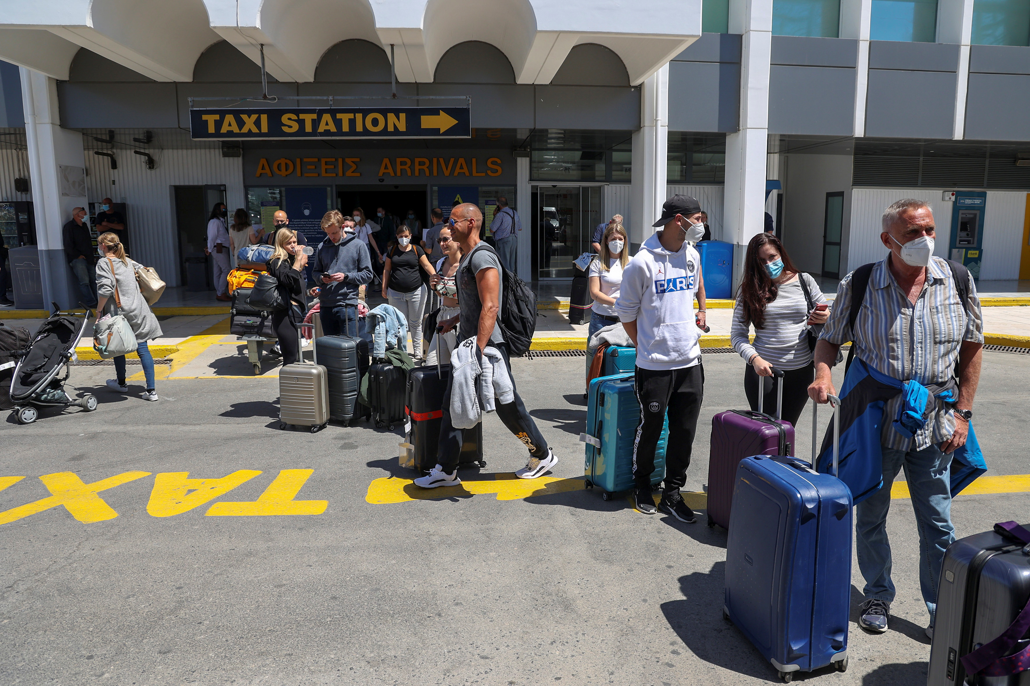 Passengers arriving from Germany and Switzerland stand with their luggage outside the terminal of the Heraklion airport, as the country's tourism season officially opens, on the island of Crete, Greece, May 15, 2021. REUTERS/Stefanos Rapanis