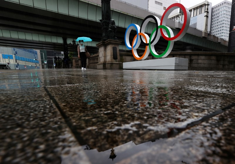 A woman wearing a protective face mask, amid the coronavirus disease (COVID-19) outbreak, walks past the Olympic Rings on the last day of Tokyo 2020 Olympic Games, in Tokyo, Japan, August 8, 2021.   REUTERS/Kim Kyung-Hoon