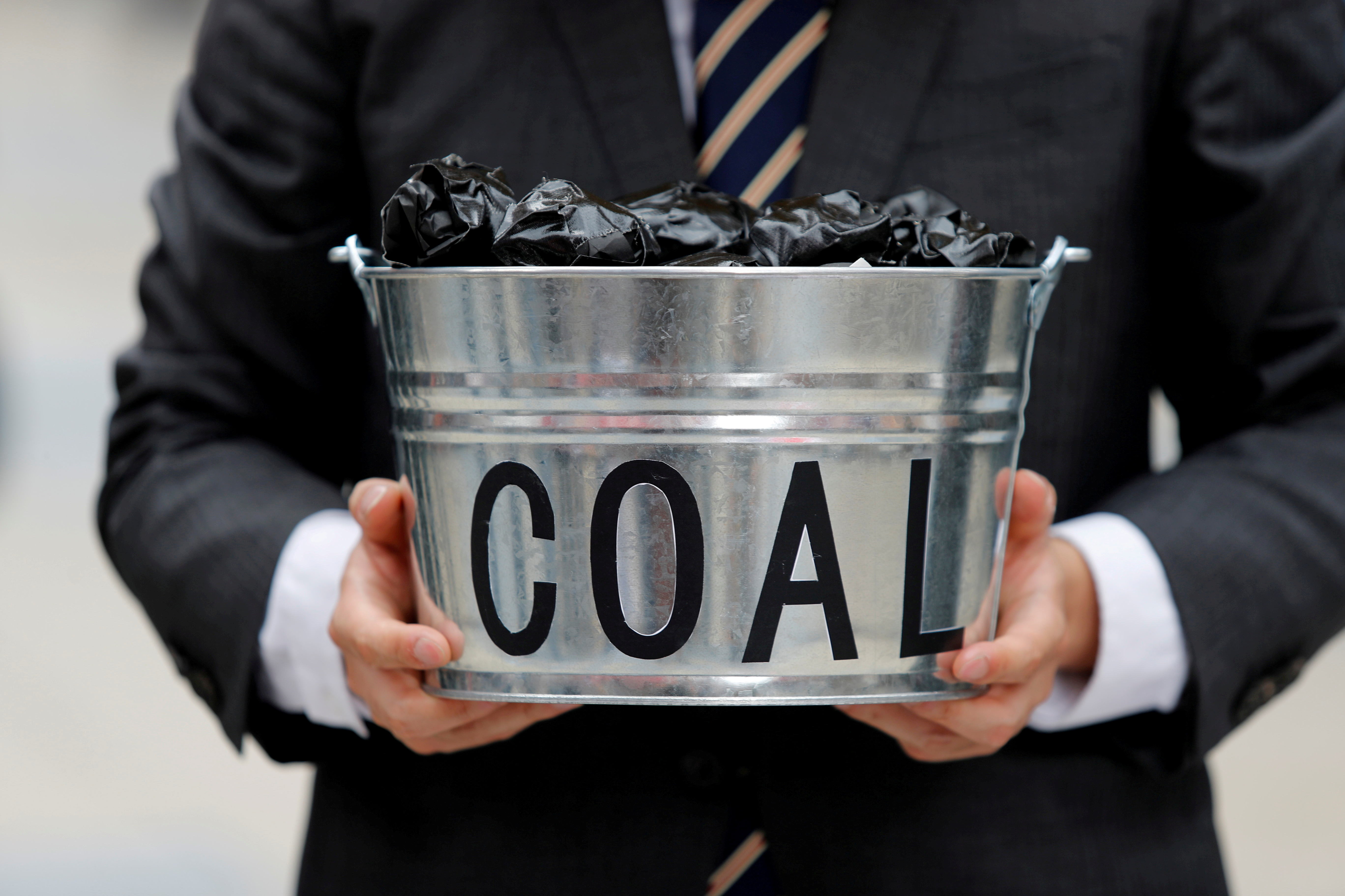 A protester holds a bucket of coal during a demonstration demanding Japan to stop supporting coal at home and overseas, at the G20 Summit in Osaka, Japan, June 28, 2019. REUTERS/Jorge Silva/File Photo