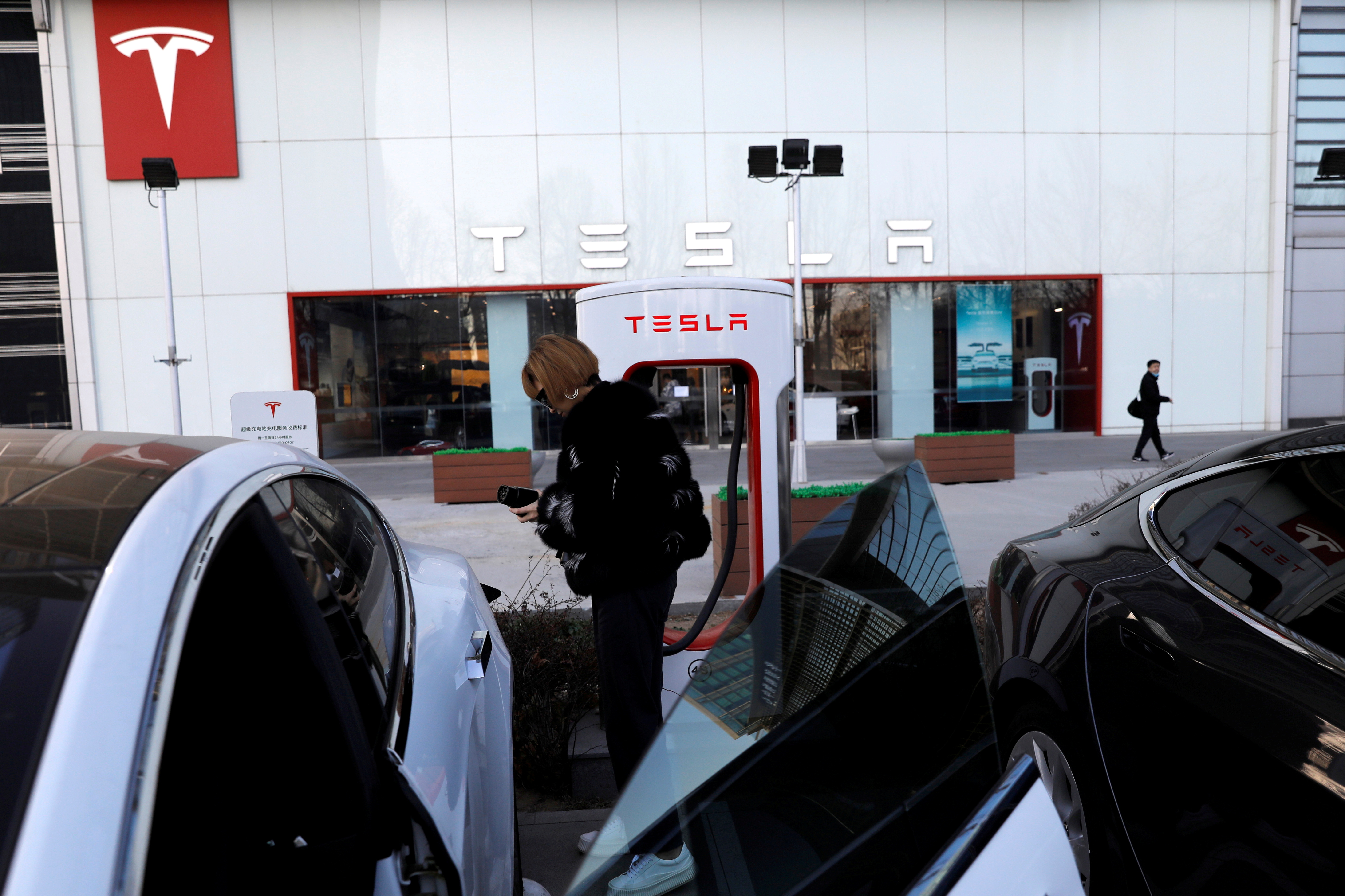 A woman charges a Tesla car in front of the electric vehicle maker's showroom in Beijing, China January 5, 2021. REUTERS/Tingshu Wang/File Photo  GLOBAL BUSINESS WEEK AHEAD