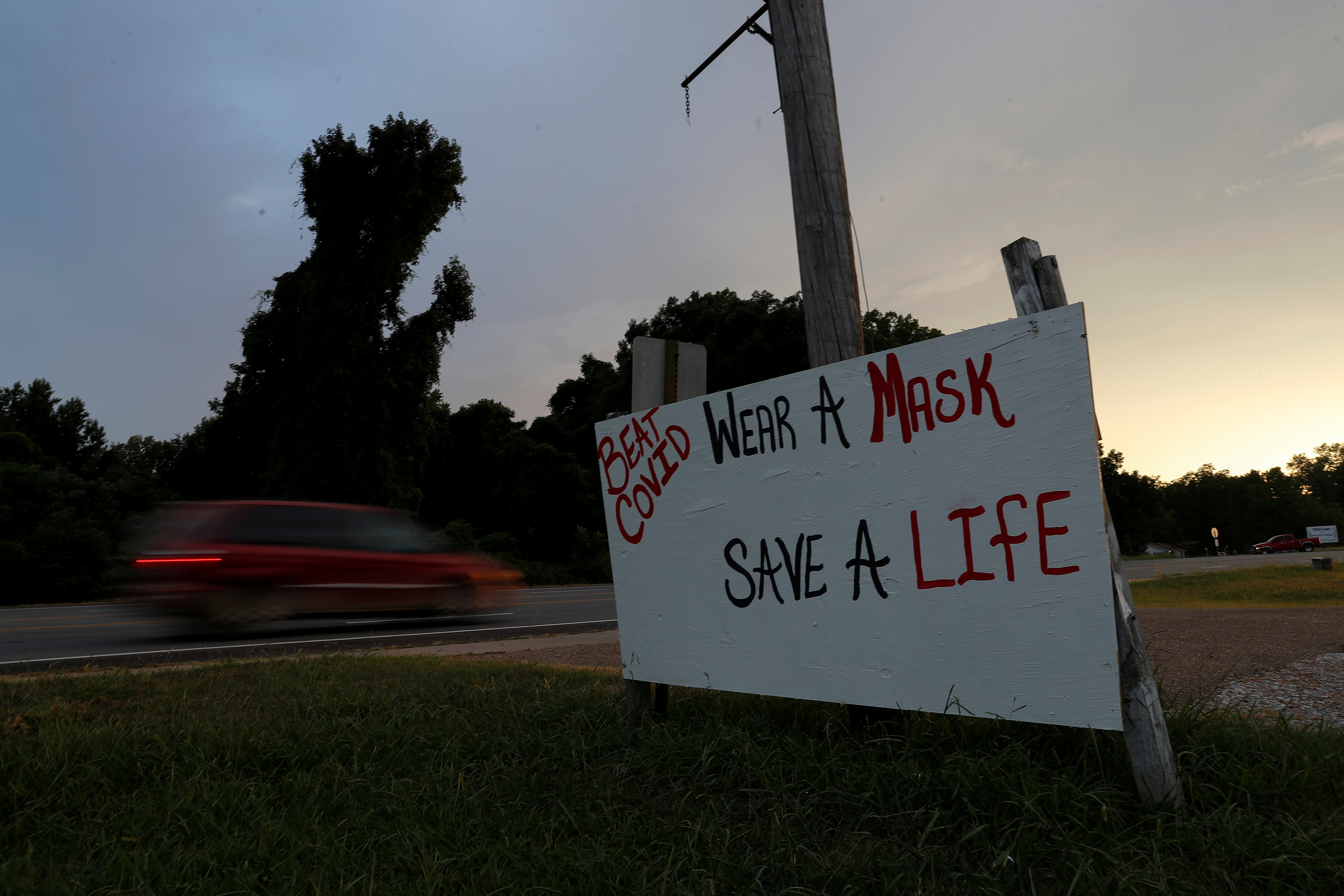 A car drives by a sign asking people to wear masks, amid the coronavirus disease (COVID19) pandemic, along U.S. Route 49 near Marvell, Arkansas, U.S., August 13, 2021. REUTERS/Shannon Stapleton