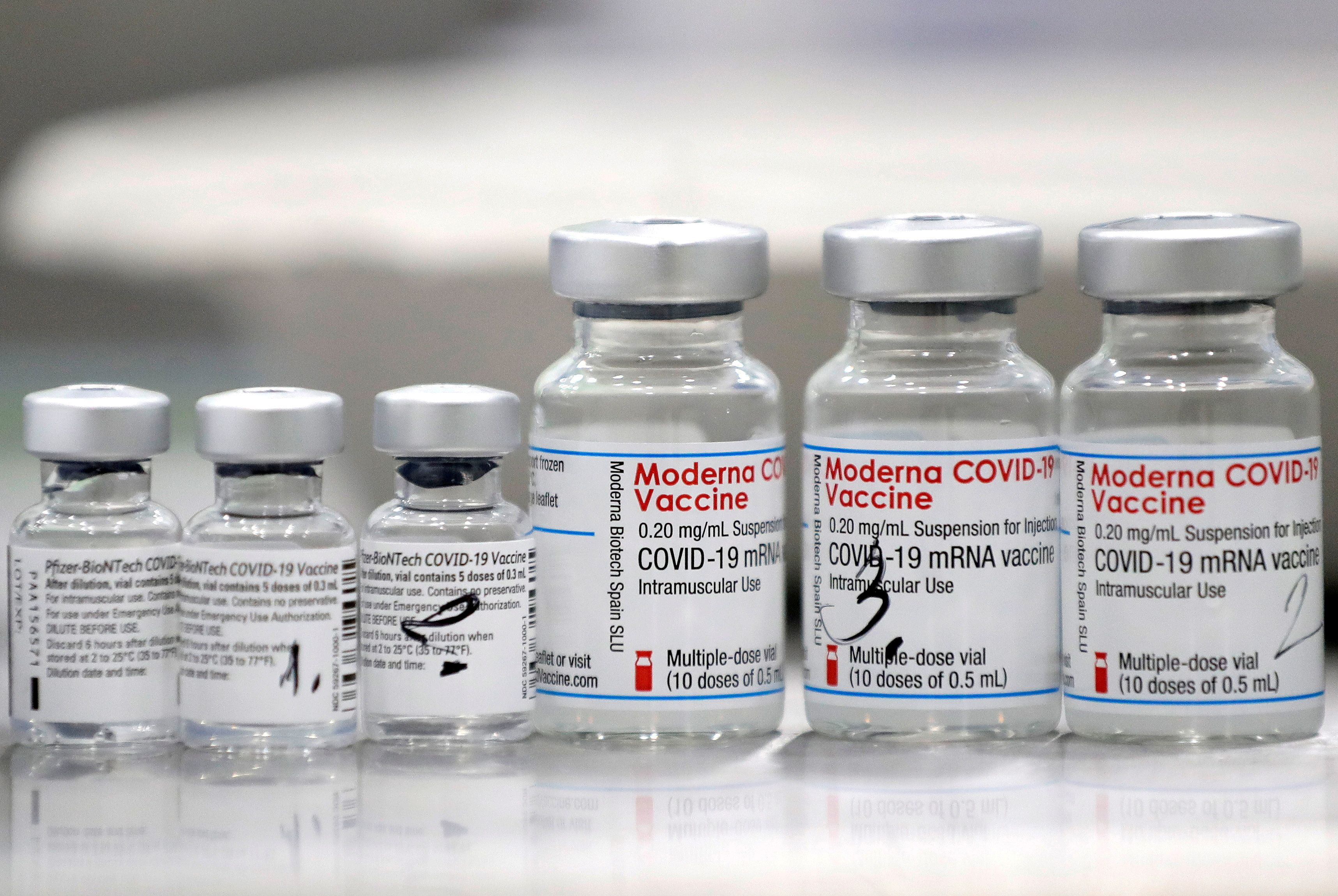 Vials of coronavirus disease (COVID-19) vaccines of Pfizer-BioNTech and Moderna are seen in the town of Ricany near Prague, Czech Republic, February 25, 2021.  REUTERS/David W Cerny/File Photo