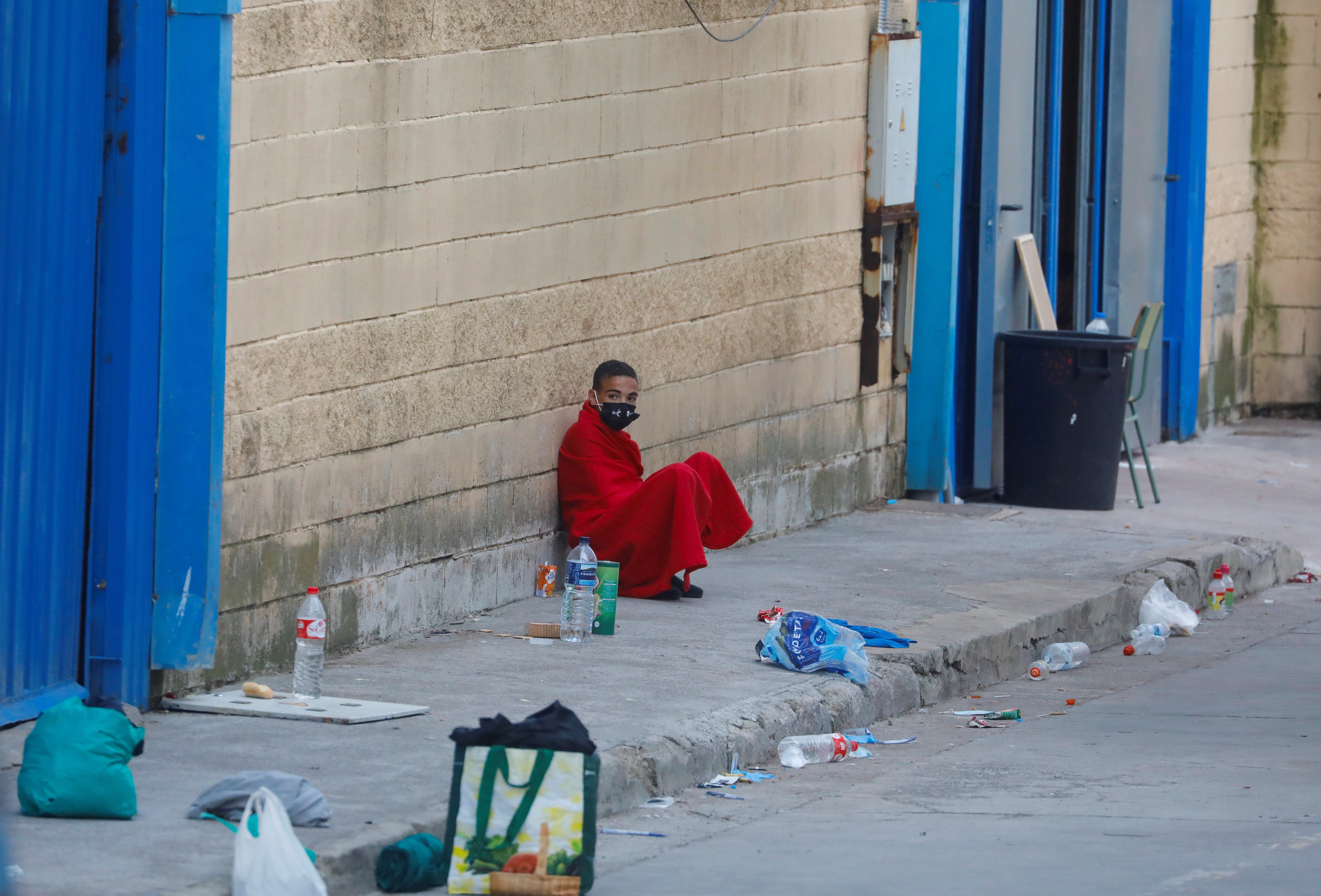 A Moroccan minor sits next to a facility prepared for migrants, after thousands of them swam across the Spanish-Moroccan during the last days, in Ceuta, Spain, May 20, 2021. REUTERS/Jon Nazca
