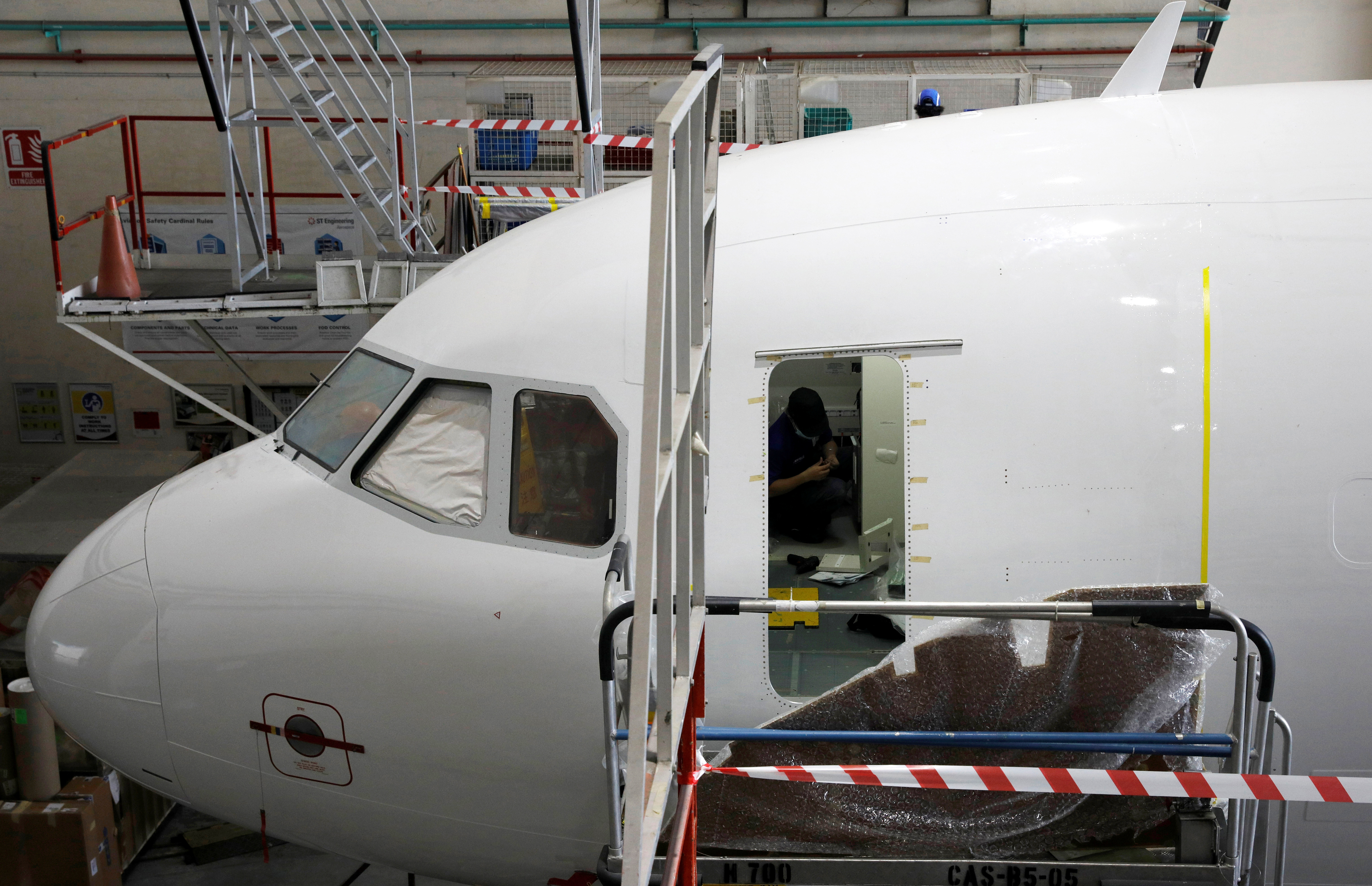 Engineers and mechanics retrofit an Airbus A321 passenger plane into a freighter plane at an ST Engineering hangar in Singapore December 2, 2020.   REUTERS/Edgar Su