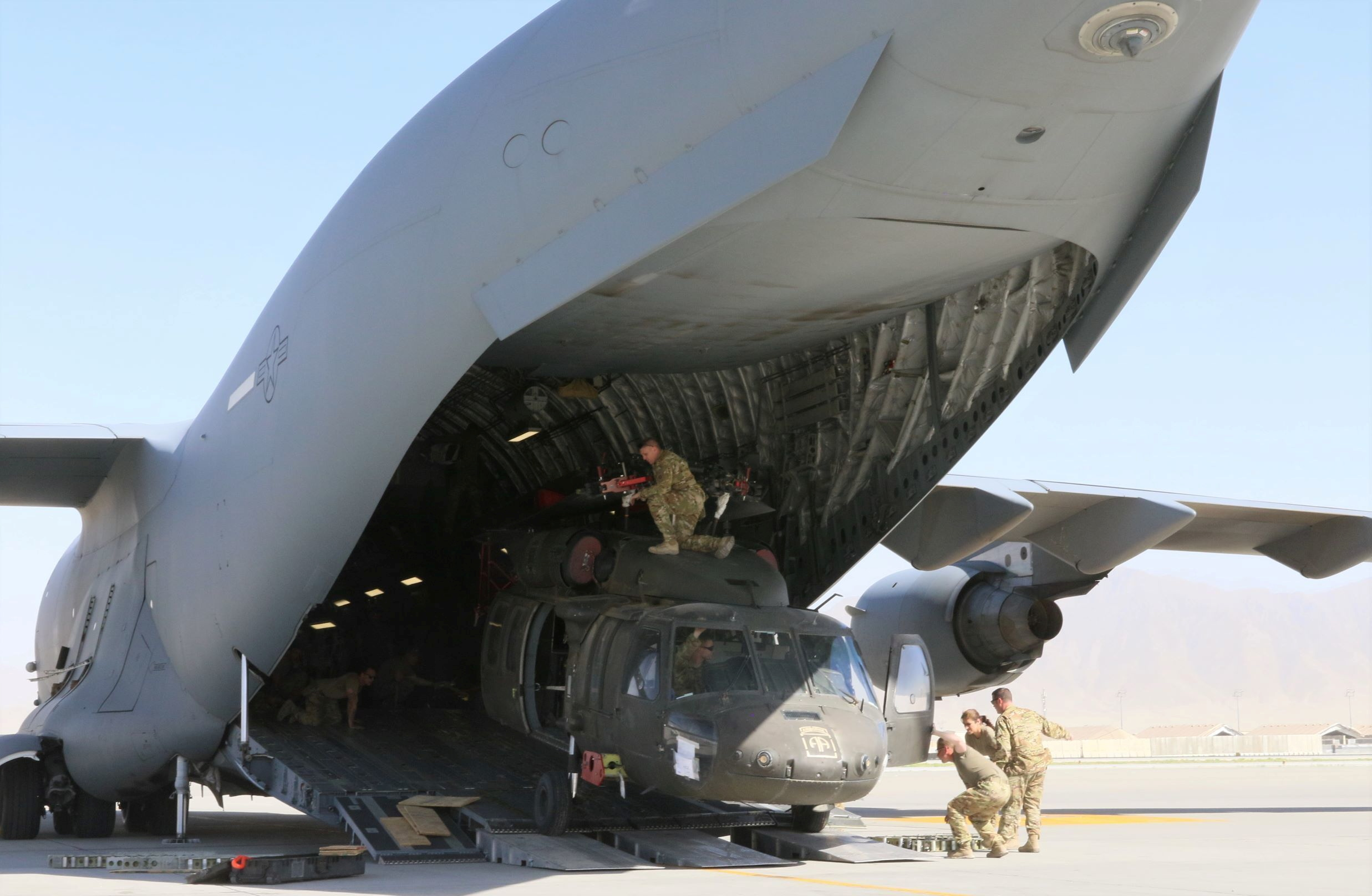 Aerial porters work with maintainers to load a UH-60L Blackhawk helicopter into a U.S. Air Force C-17 Globemaster III during the withdrawl of American forces in Afghanistan, June 16, 2021. Picture taken June 16, 2021. U.S. Army/Sgt. 1st Class Corey Vandiver/Handout via REUTERS