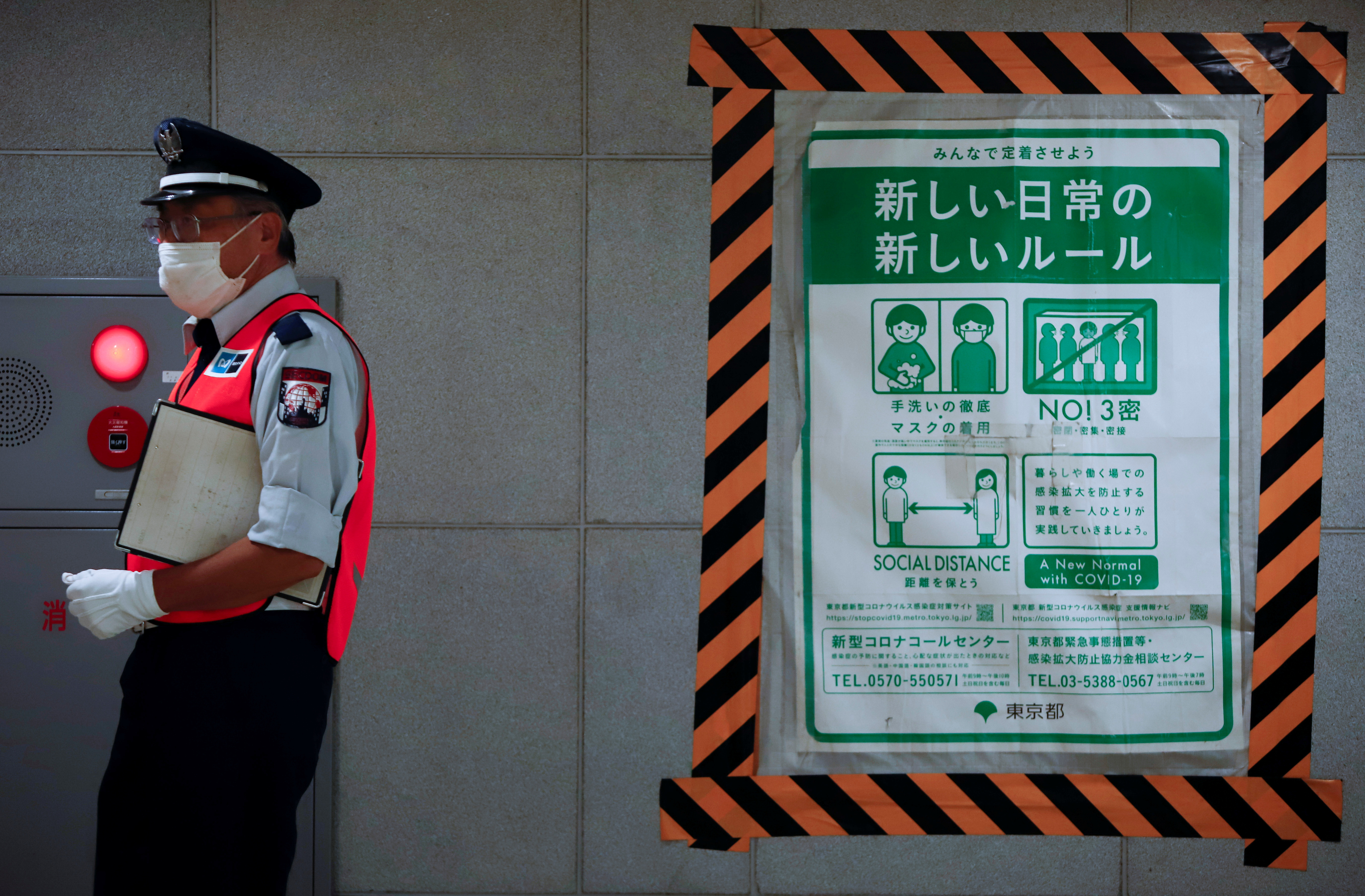 A station employee walks by a coronavrius disease (COVID-19) infection prevention instructions sign at a Tokyo metro station in Tokyo, Japan. July 30, 2021 REUTERS/AndronikiChristodoulou