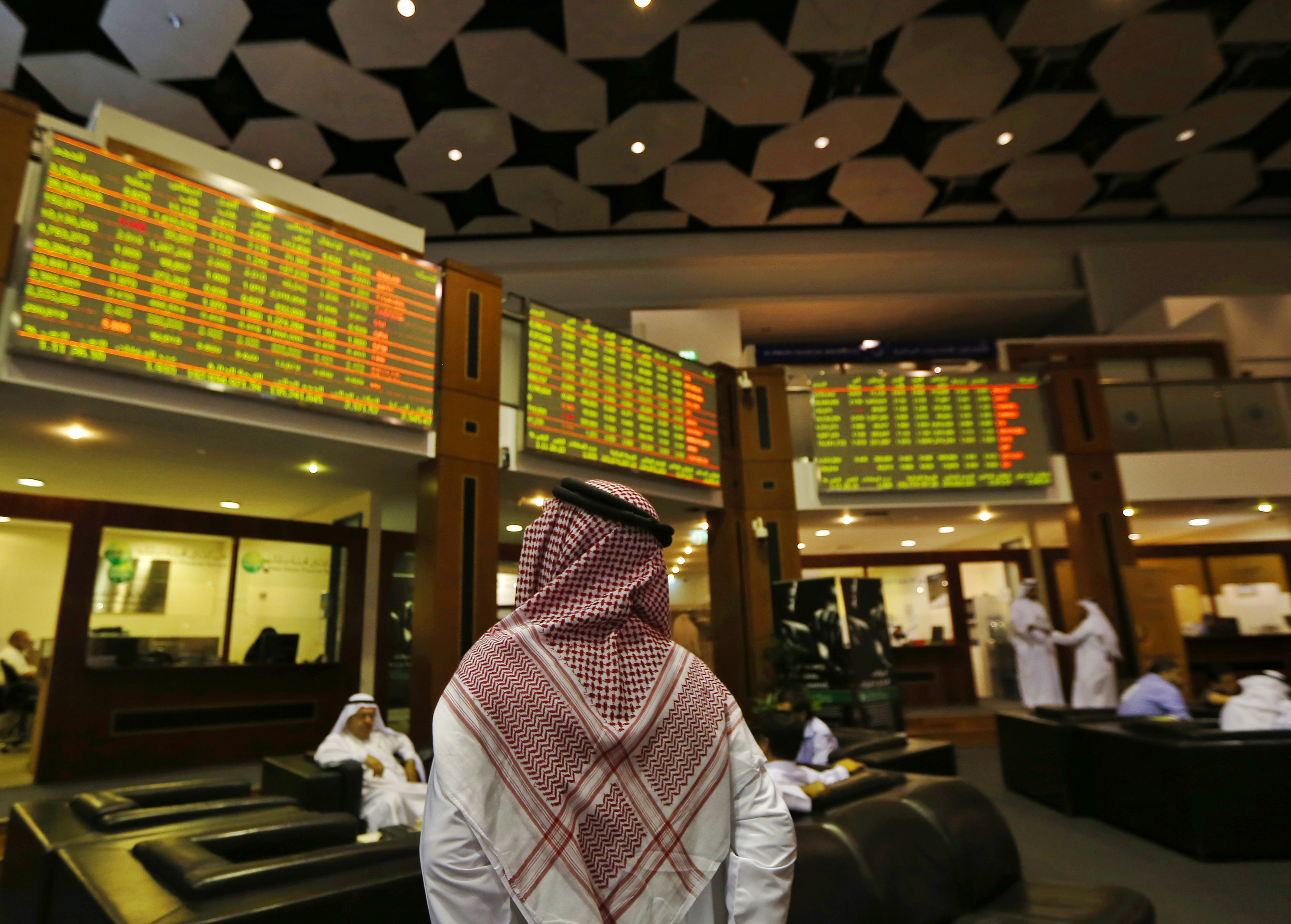 An investor looks up at screens displaying stock information at the Dubai Financial Market, June 17, 2013. The United Arab Emirates has revived a proposal to merge its two main stock exchanges in a state-backed deal that could boost trade in the local market and attract more foreign investment to the Gulf state, sources familiar with the plan said. REUTERS/Jumana El Heloueh