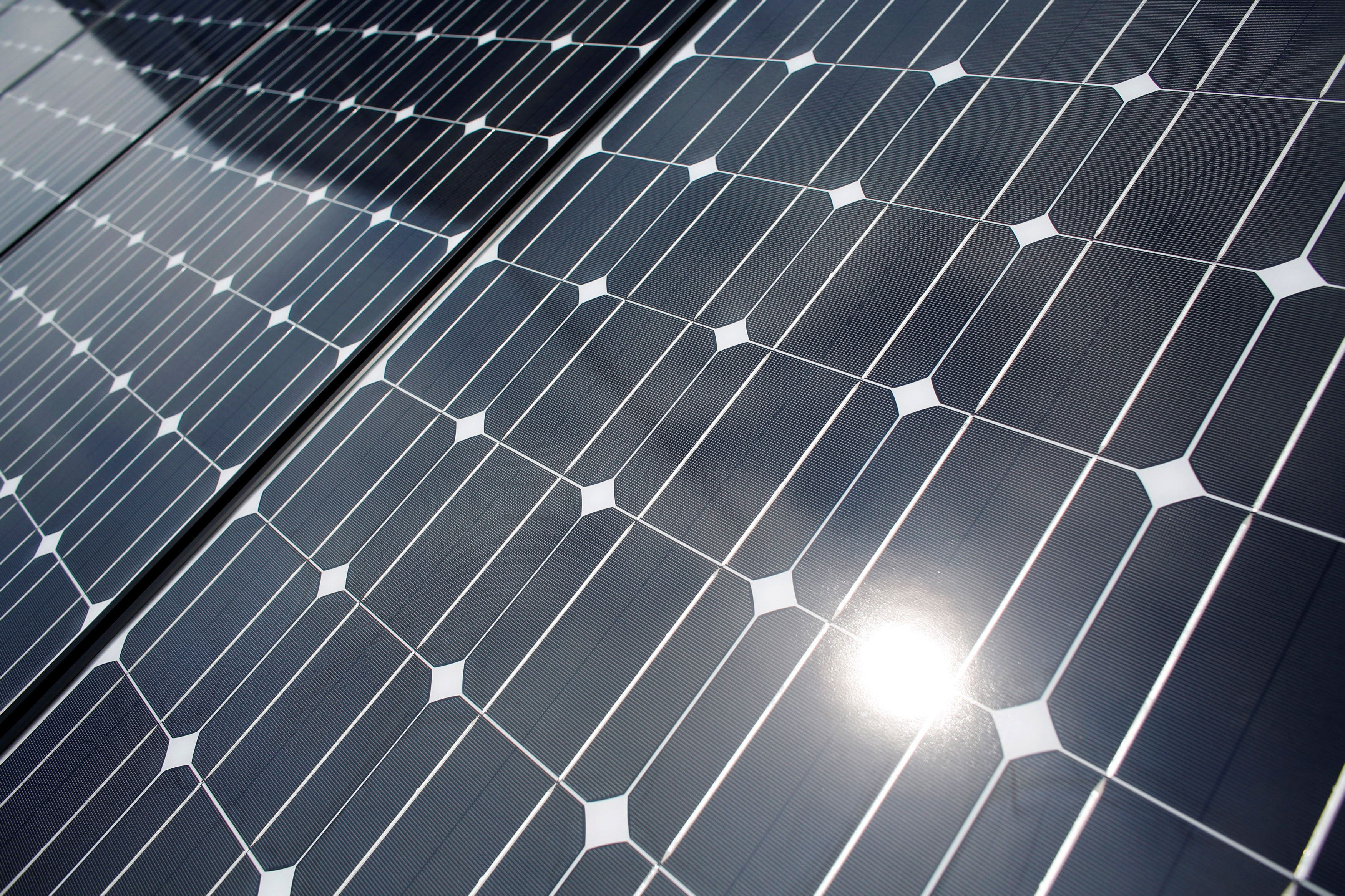 The sun is reflected on a solar panel at a solar power field in Kawasaki, near Tokyo June 13, 2012. REUTERS/Toru Hanai/File Photo