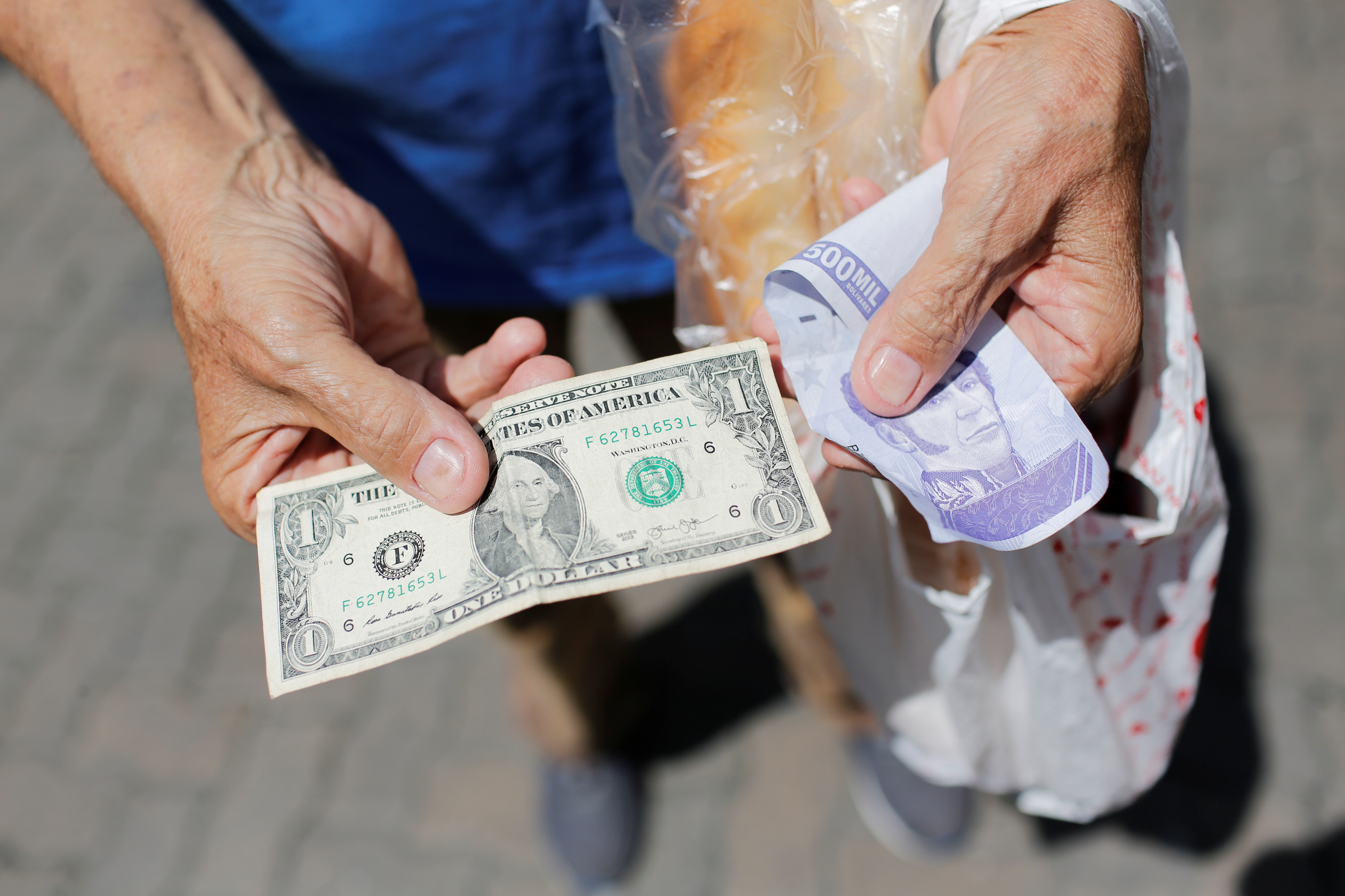 A street vendor holds a one dollar banknote beside an old Bolivar banknote in Caracas, Venezuela, October 1, 2021. REUTERS/Manaure Quintero
