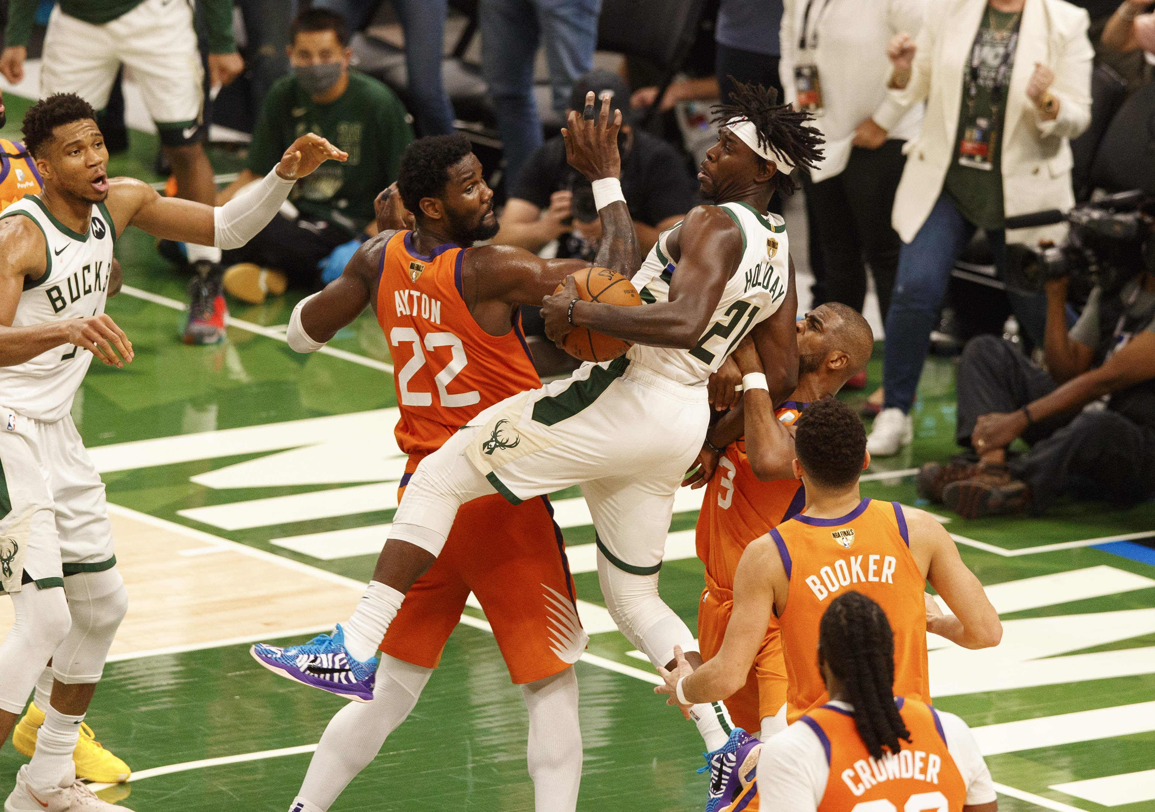 Jul 14, 2021; Milwaukee, Wisconsin, USA; Milwaukee Bucks guard Jrue Holiday (21) grabs the ball behind Phoenix Suns center Deandre Ayton (22) during the fourth quarter during game four of the 2021 NBA Finals at Fiserv Forum. Mandatory Credit: Jeff Hanisch-USA TODAY Sports