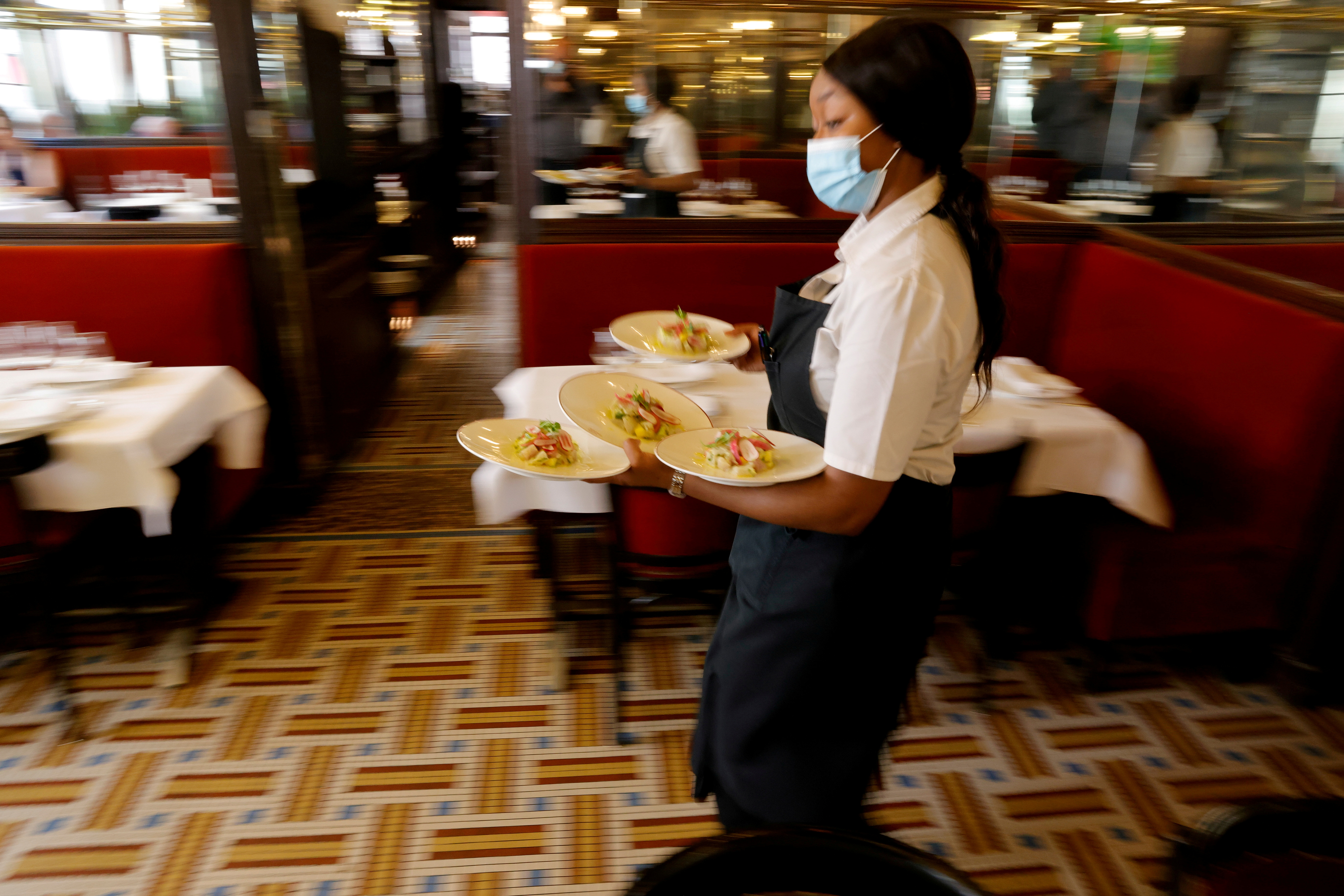 A waiter serves dishes in a dining room at Au Petit Riche restaurant in Paris as cafes, bars and restaurants reopen indoor dining rooms in France, June 9, 2021. REUTERS/Pascal Rossignol/File Photo
