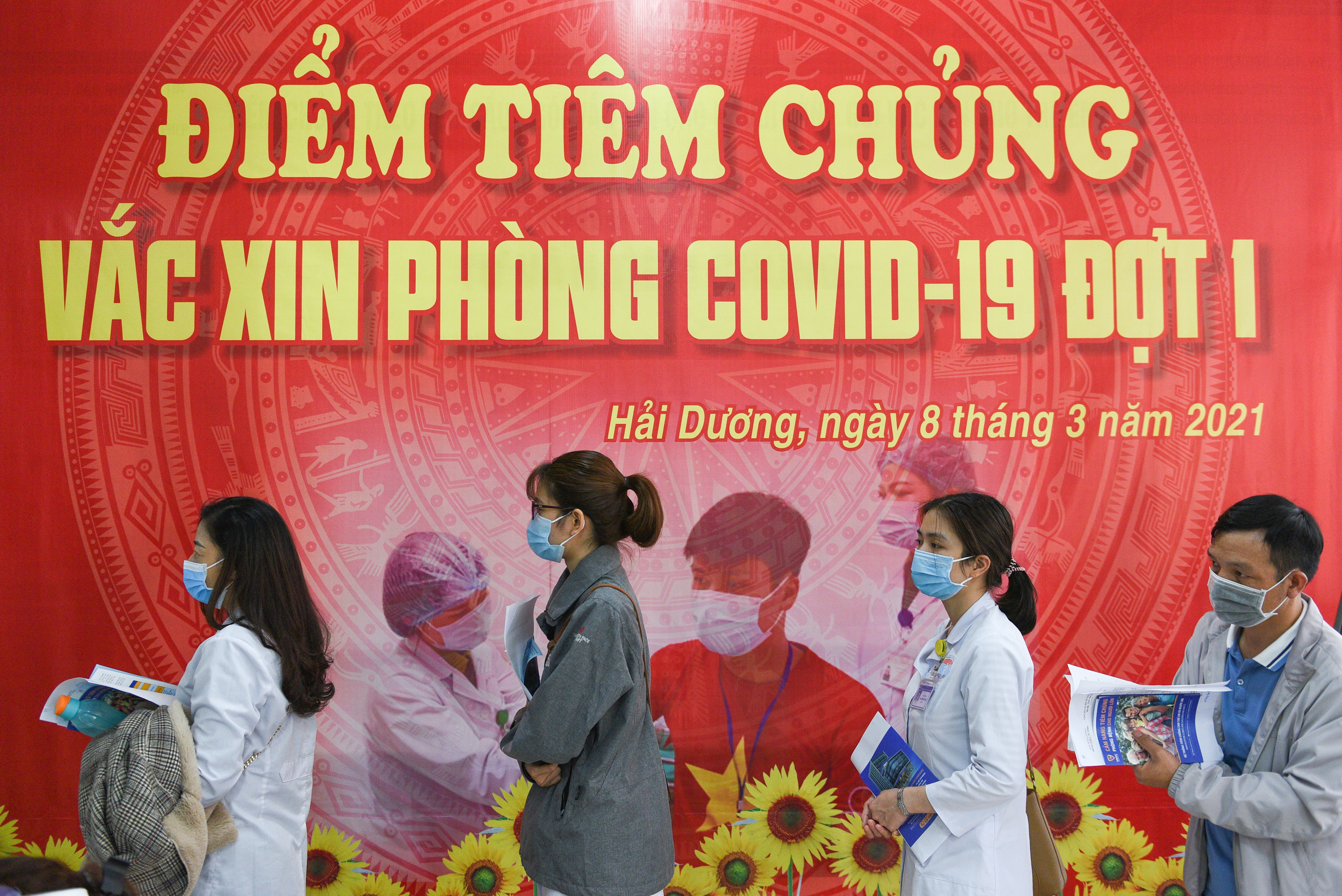 Health workers wait for their turn as Vietnam starts its official rollout of AstraZeneca's coronavirus disease (COVID-19) vaccine for health workers, at Hai Duong Hospital for Tropical Diseases, Hai Duong province, Vietnam, March 8, 2021. REUTERS/Thanh Hue/Files