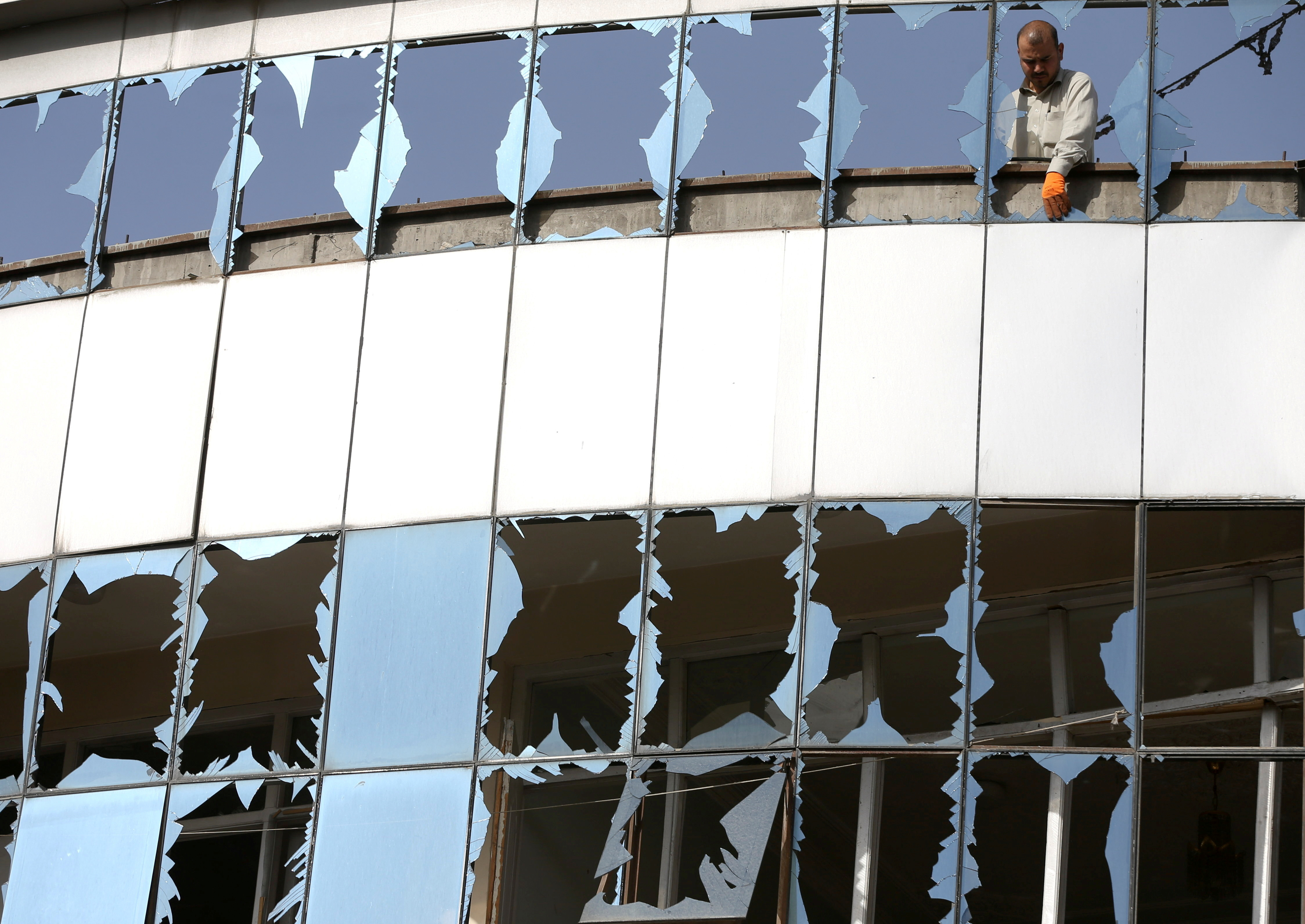 A man removes broken glasses from a window at the site of yesterday's night-time car bomb blast in Kabul, Afghanistan August 4, 2021. REUTERS/Stringer