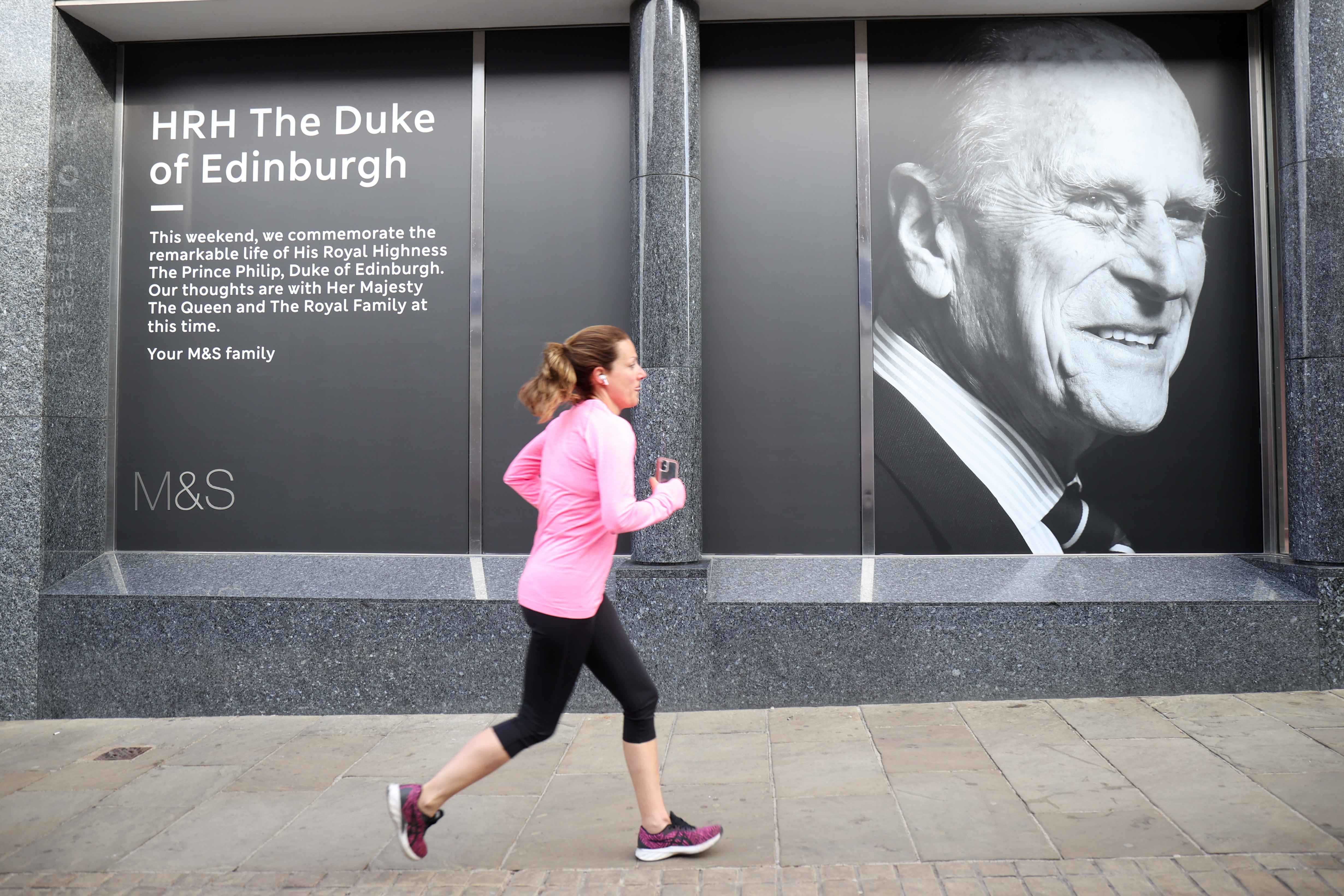 A woman runs in front of a shop with a sign of Britain's Prince Philip, who died at the age of 99, in Windsor, near London, Britain, April 16, 2021. REUTERS/Molly Darlington