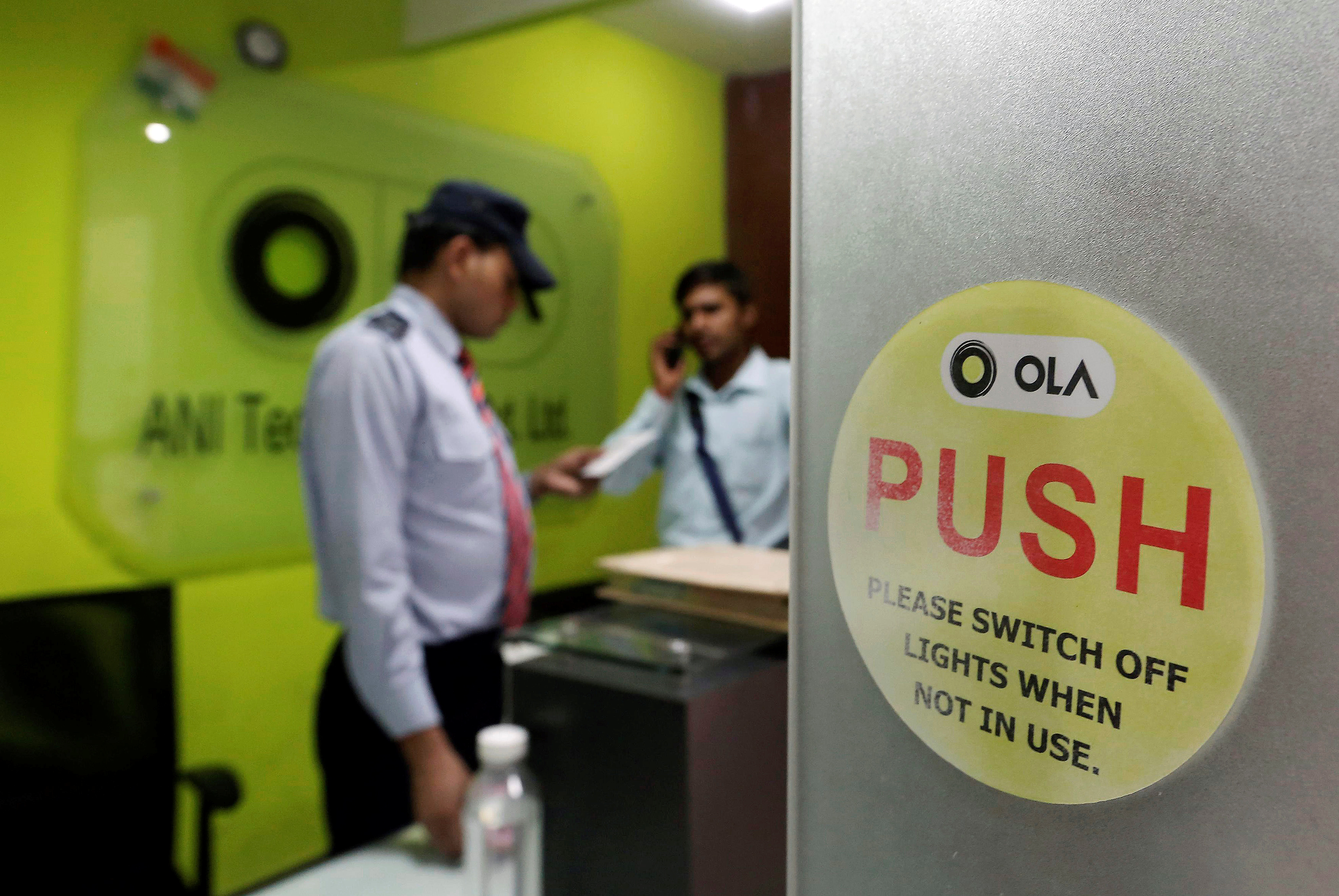 An employee speaks over his phone as a private security guard looks on at the front desk inside the office of Ola cab service in Gurugram, previously known as Gurgaon, on the outskirts of New Delhi, India, April 20, 2016. REUTERS/Anindito Mukherjee/Files