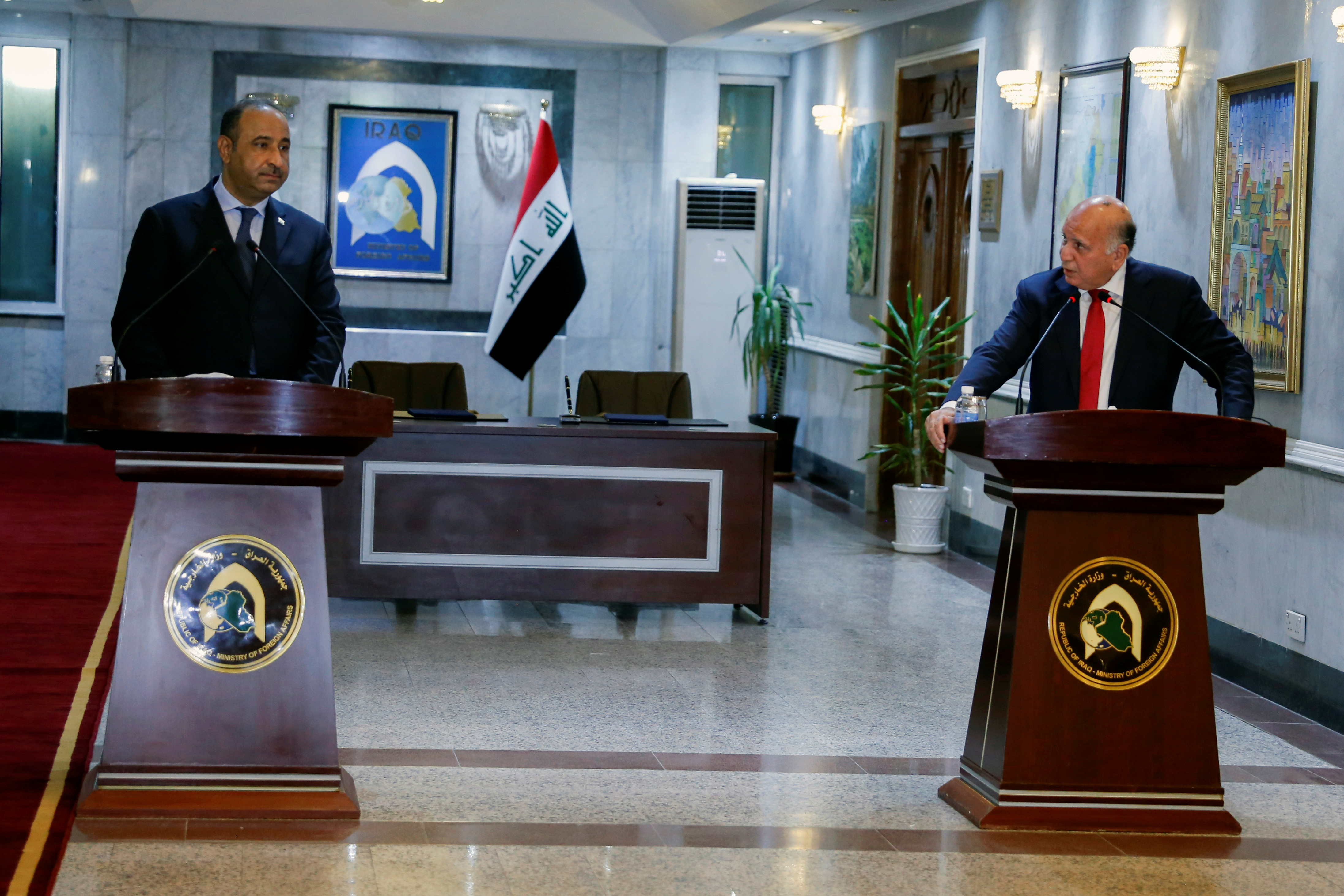 Iraqi Foreign Minister Fouad Hussein speaks with Iraqi Culture Minister Hassan Nadhim during a news conference at the Ministry of Foreign Affairs in Baghdad, Iraq August 3, 2021. REUTERS/Saba Kareem