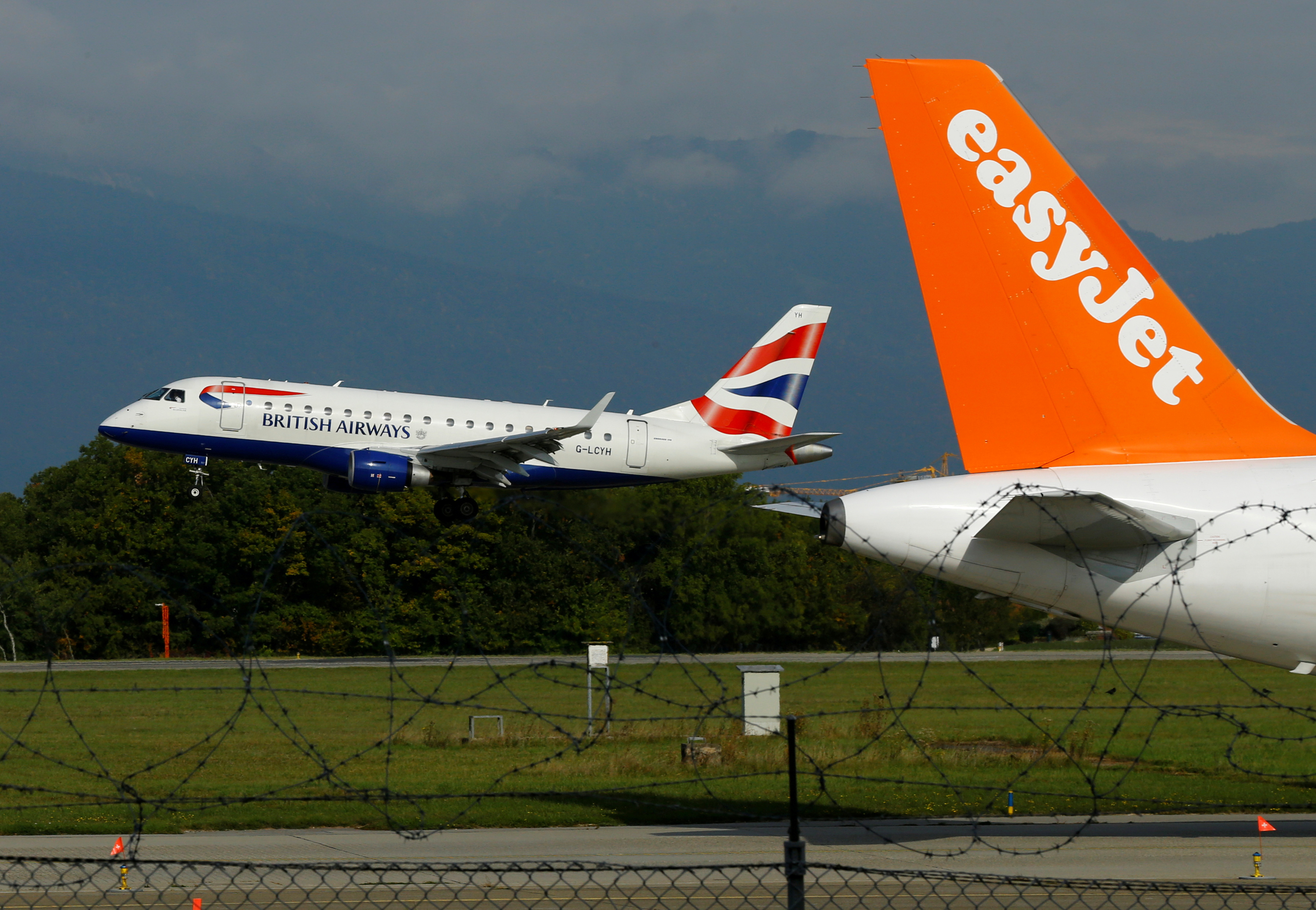 A British Airways Embraer ERJ-170STD aircraft lands next to a EasyJet plane ready for take off at Cointrin airport in Geneva, Switzerland September 26, 2017.  REUTERS/Denis Balibouse/File Photo