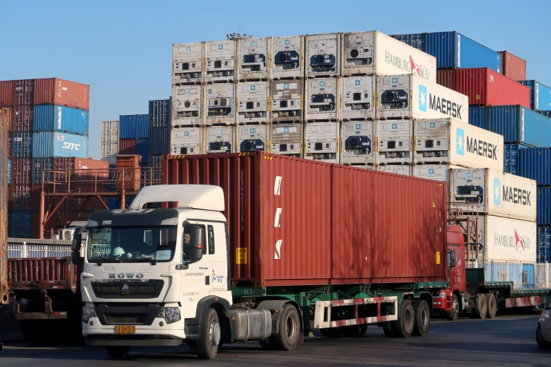 A worker drives a truck carrying a container at a logistics center near Tianjin port, in Tianjin, China December 12, 2019.   REUTERS/Yilei Sun/File Photo