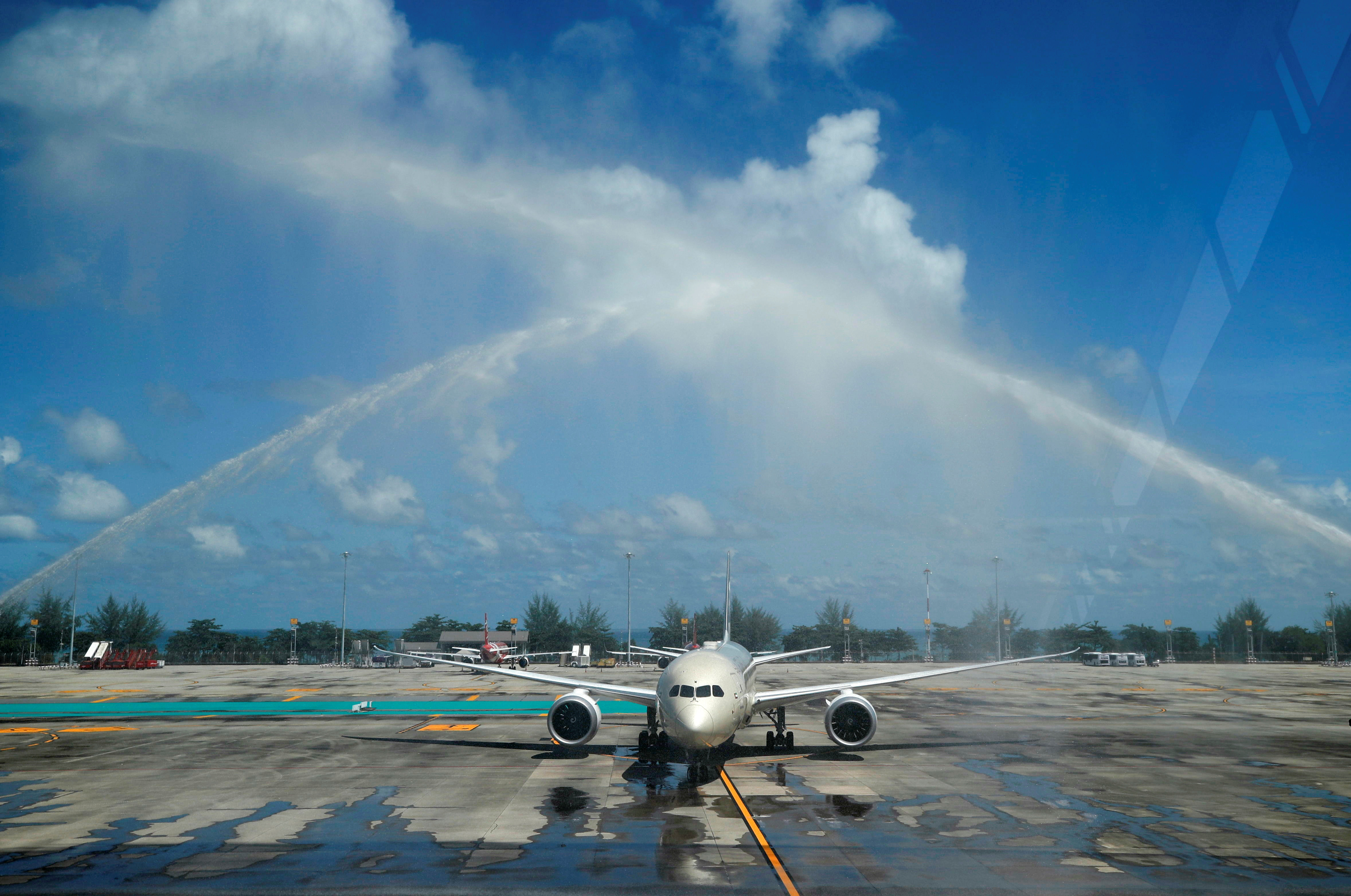 A plane carrying the first foreign tourists to arrive at the airport as Phuket reopens to overseas tourists, allowing foreigners fully vaccinated against the coronavirus disease (COVID-19) to visit the resort island without quarantine, receives a water cannon salute from fire trucks in Phuket, Thailand July 1, 2021. REUTERS/Jorge Silva
