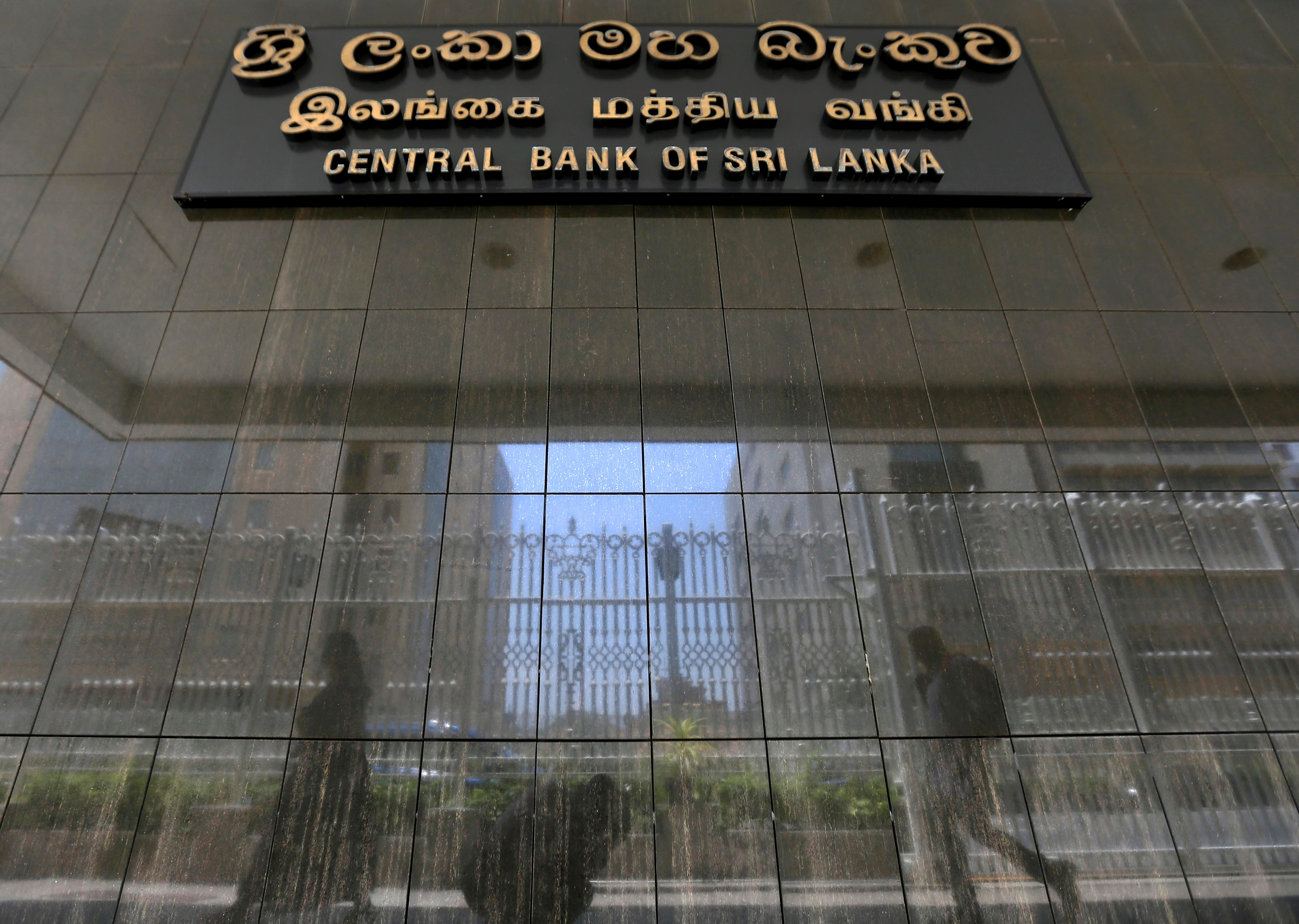 People walk past the main entrance of the Sri Lanka's Central Bank in Colombo, Sri Lanka March 24, 2017. REUTERS/Dinuka Liyanawatte/File Photo