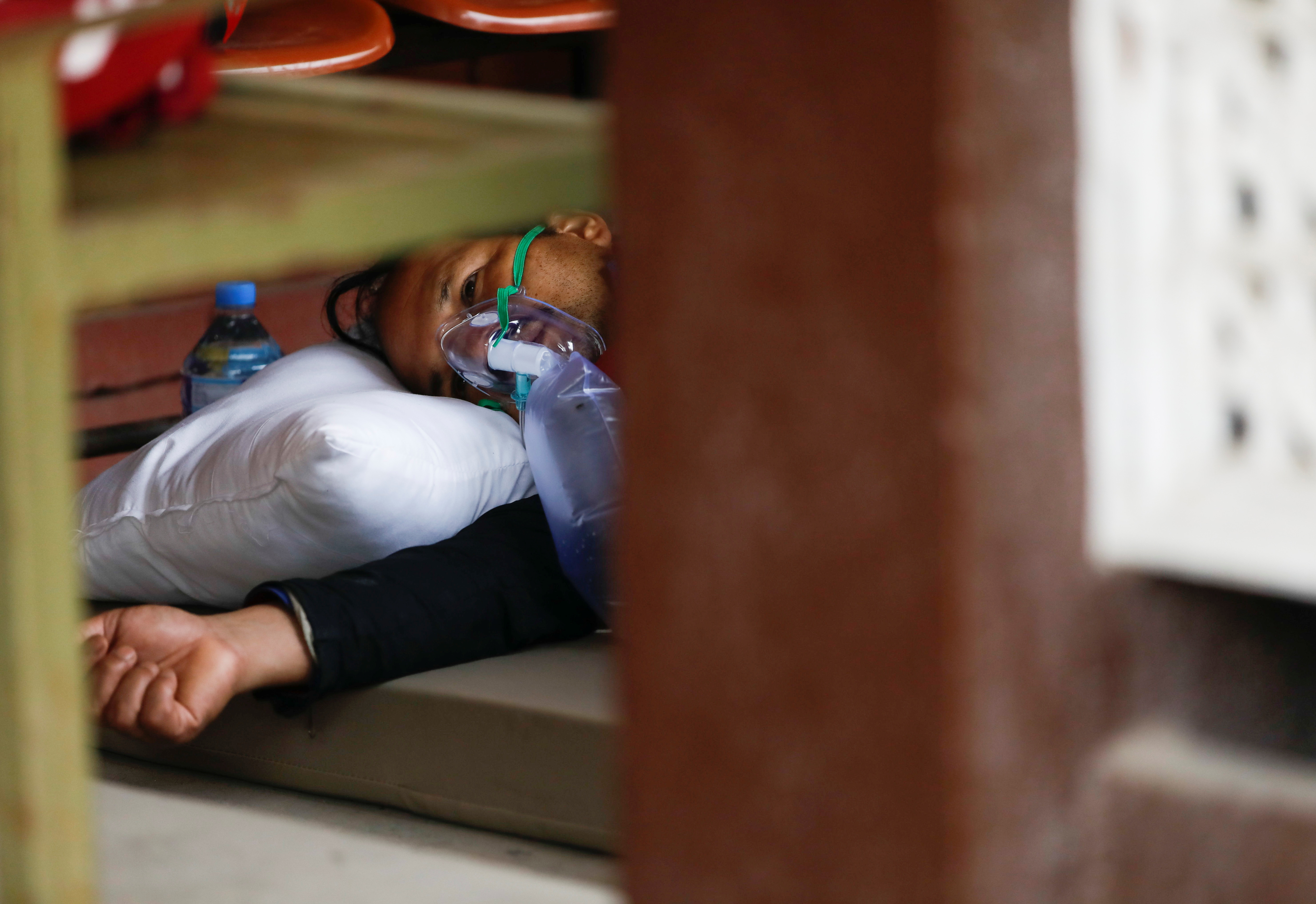 A patient receives oxygen as he lays on the floor outside the passage of a hospital due to a lack of free beds at the hospital for coronavirus disease (COVID-19) patients, as the second major coronavirus wave surges in Kathmandu, Nepal, May 10, 2021. REUTERS/Navesh Chitrakar