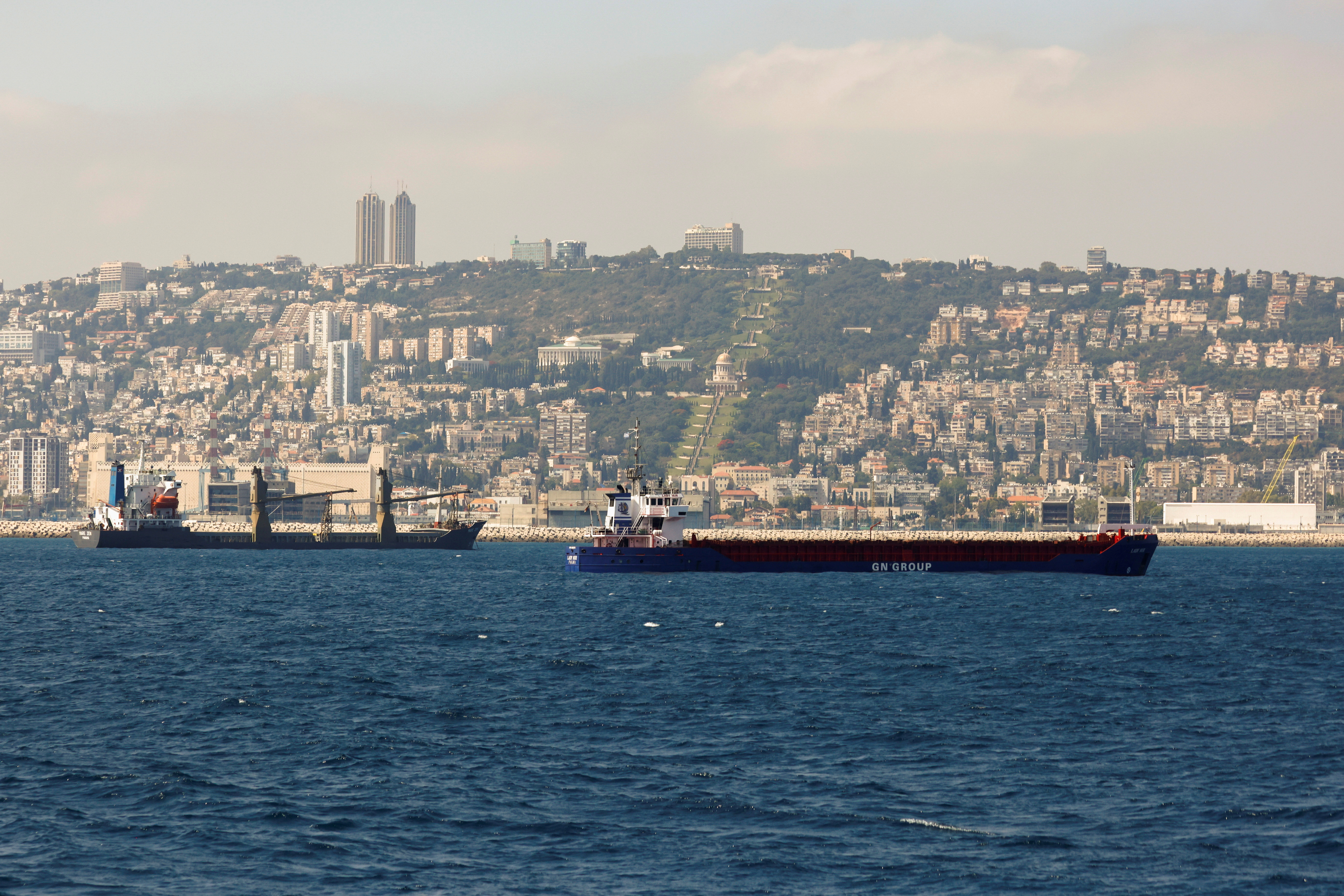 The city of Haifa is seen in the background as ships sail in the Mediterranean Sea, in the Haifa bay area, northern Israel June 9, 2021.