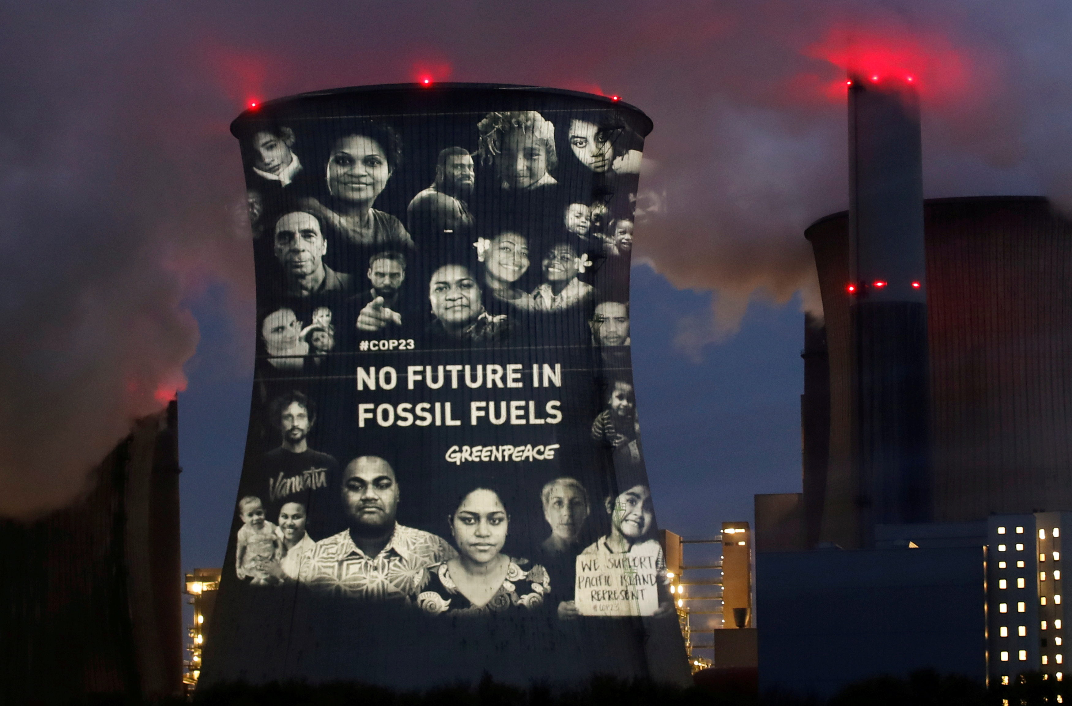 Activists of the environmental organisation Greenpeace project a slogan that reads