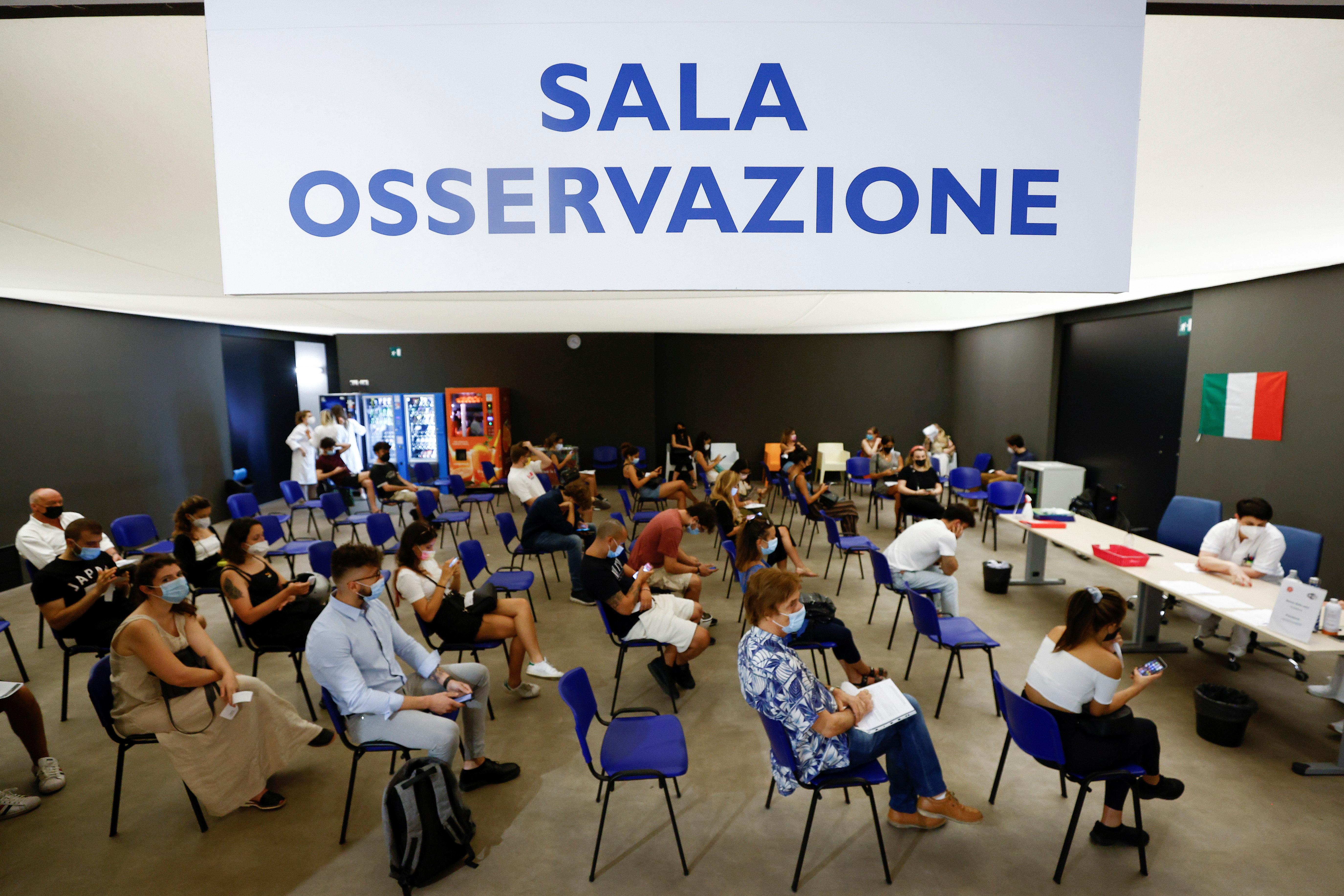 People wait in the observation room after receiving a dose of the Moderna vaccine against the coronavirus disease (COVID-19), a day before the wider Green Pass restrictions, where Italians will need proof of immunity to access an array of services and leisure activities, come into force, at the Music Auditorium in Rome, Italy, August 5, 2021. REUTERS/Guglielmo Mangiapane