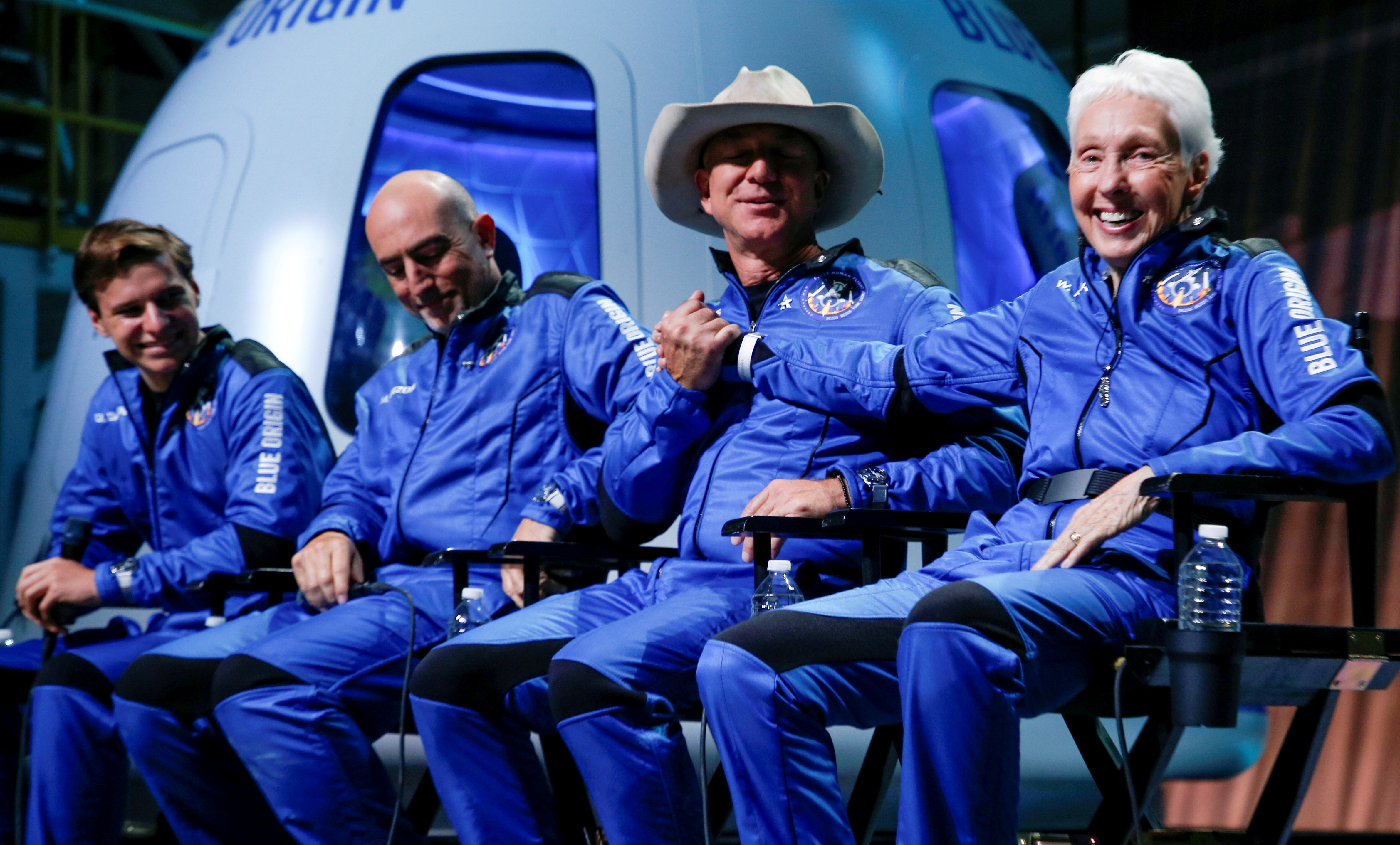 Billionaire American businessman Jeff Bezos (3rd-L) shakes hands with Wally Funk, who became the oldest person in space with other crew mates Oliver Daemen (L) and Mark Bezos (2nd-L) at a post-launch press conference after they flew on Blue Origin's inaugural flight to the edge of space, in the nearby town of Van Horn, Texas, U.S. July 20, 2021.   REUTERS/Joe Skipper