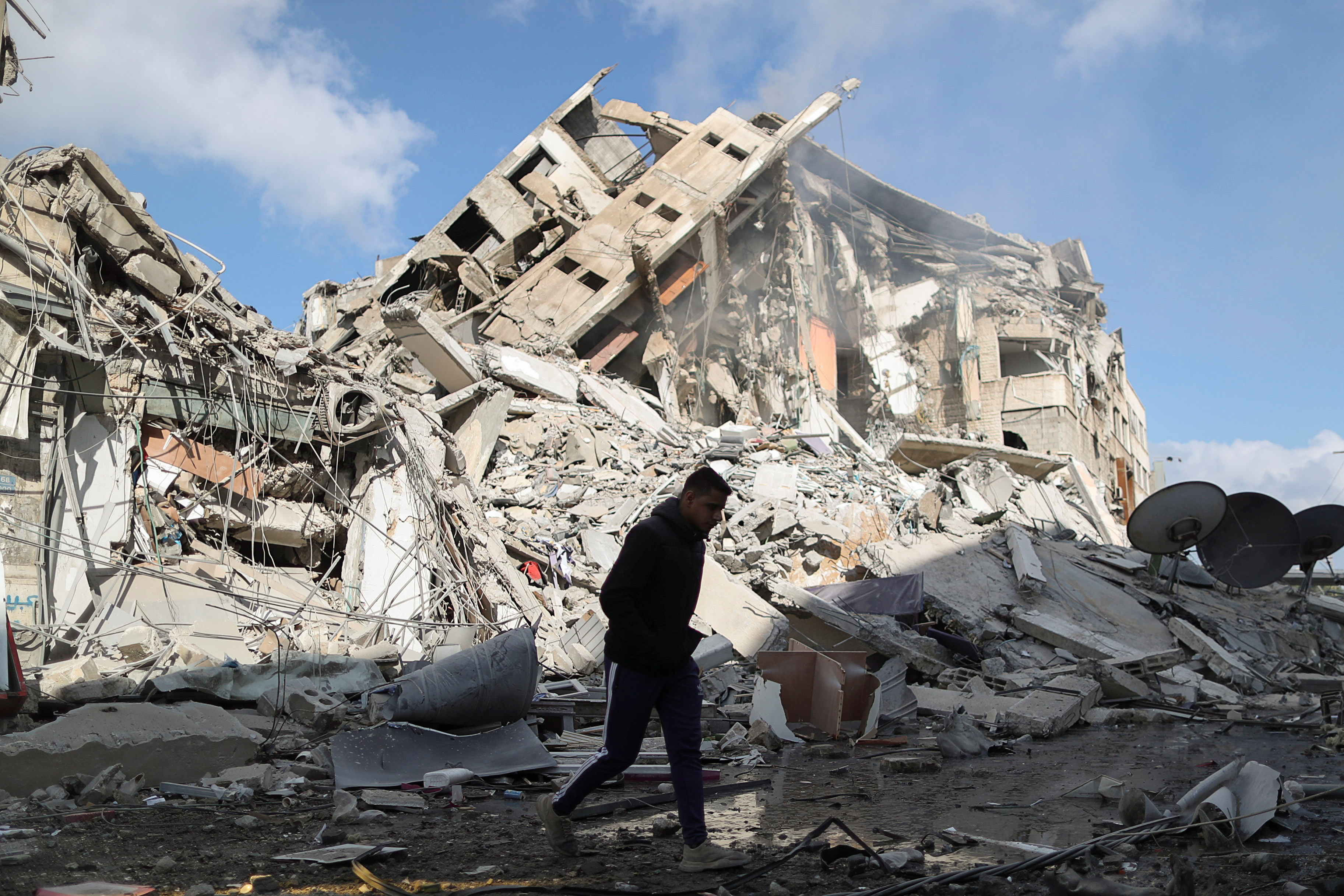 A Palestinian man walks past the remains of a tower building which was destroyed by Israeli air strikes, amid a flare-up of Israeli-Palestinian violence, in Gaza City May 13, 2021. REUTERS/Suhaib Salem