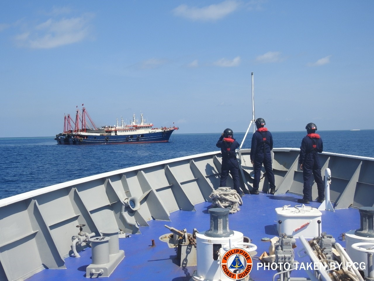 Philippine Coast Guard personnel survey several ships believed to be Chinese militia vessels in Sabina Shoal in the South China Sea, in a handout photo distributed by the Philippine Coast Guard on May 5 and taken according to source on April 27, 2021. Philippine Coast Guard/Handout via REUTERS