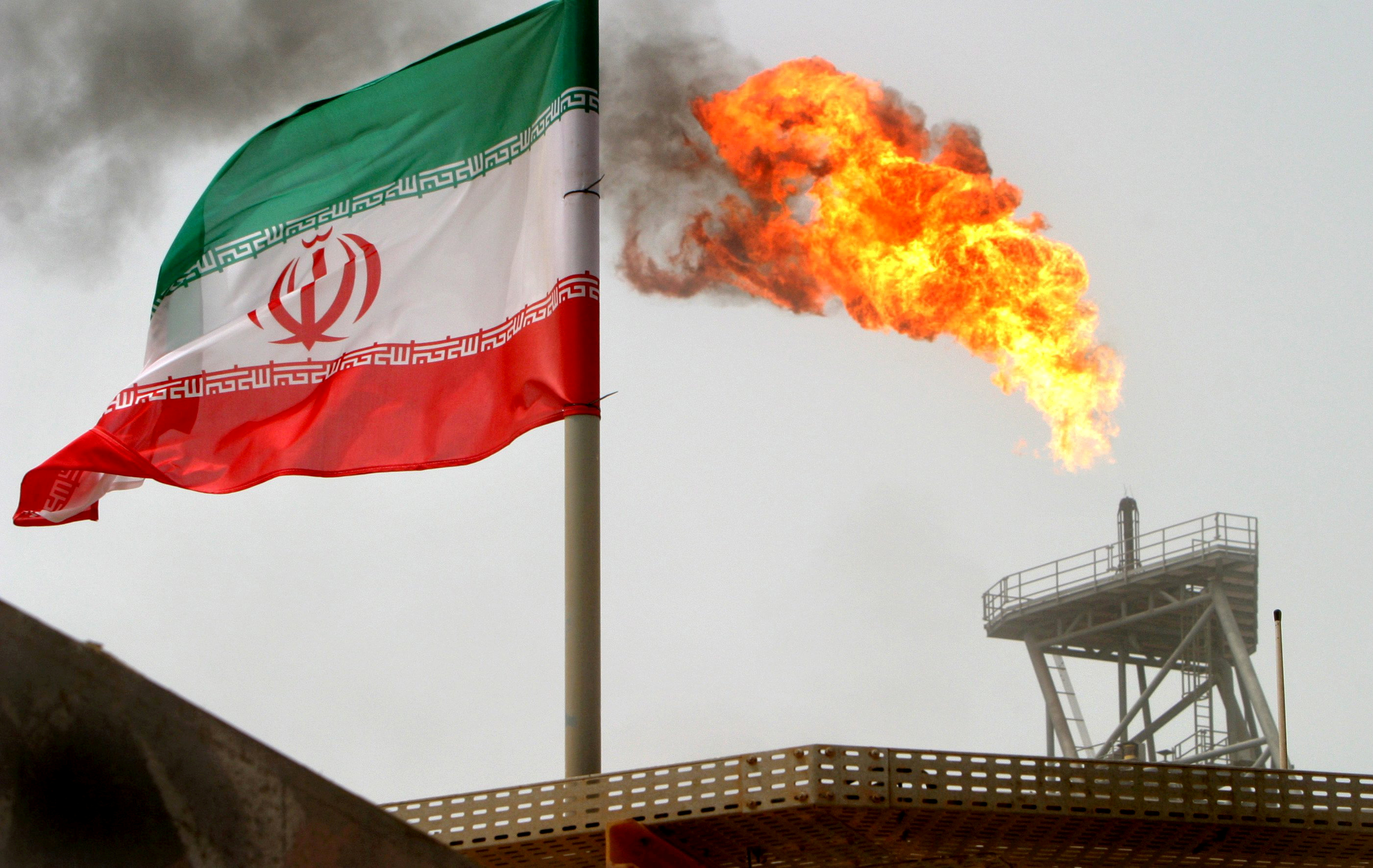A gas flare on an oil production platform is seen alongside an Iranian flag in the Gulf July 25, 2005. REUTERS/Raheb Homavandi