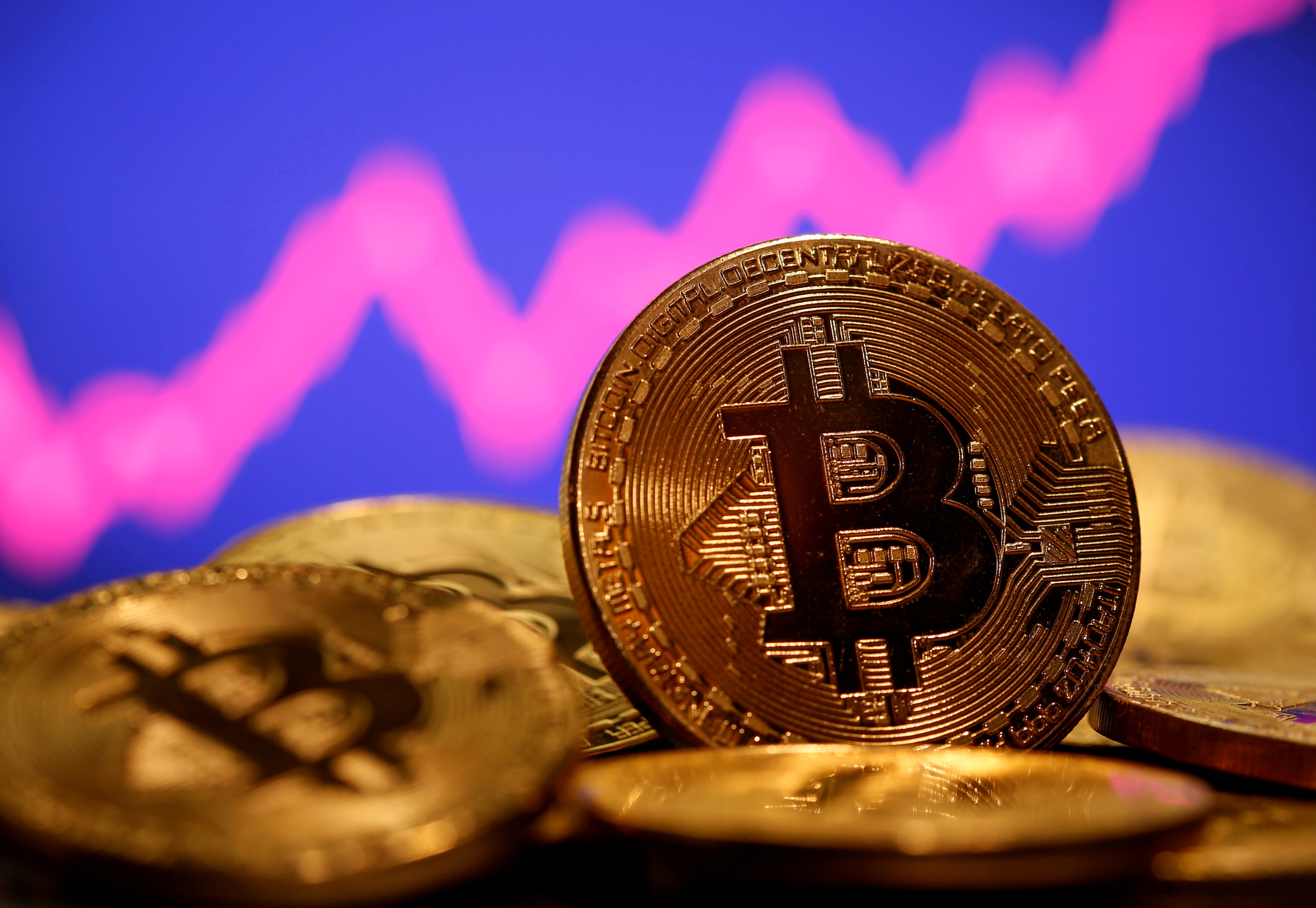 A representation of virtual currency Bitcoin is seen in front of a stock graph in this illustration taken January 8, 2021. REUTERS/Dado Ruvic