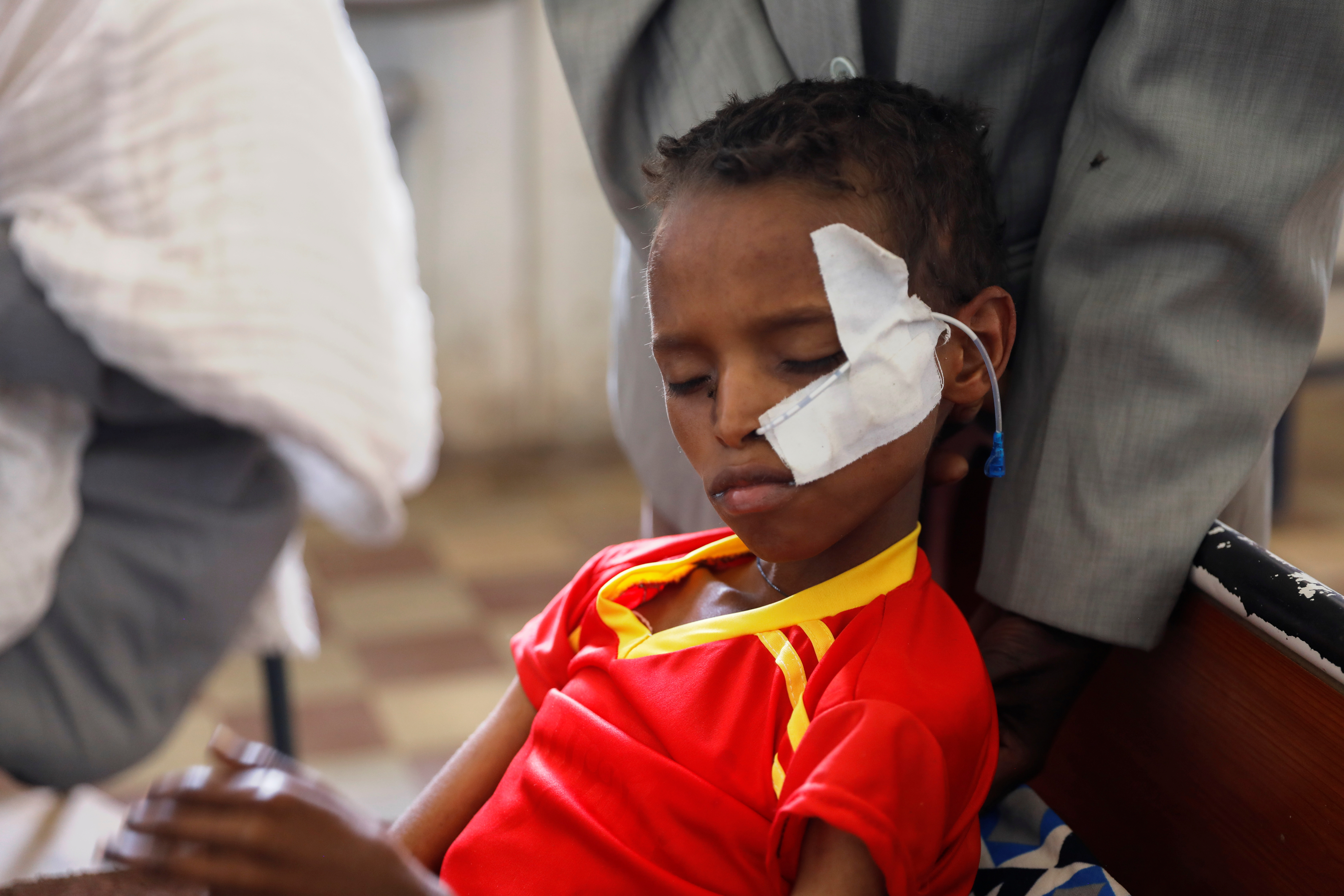 Fourteen-year-old Adan Muez is helped to sit up in his bed at Adigrat General Hospital in the town of Adigrat, Tigray region, Ethiopia, March 18, 2021. REUTERS/Baz Ratner