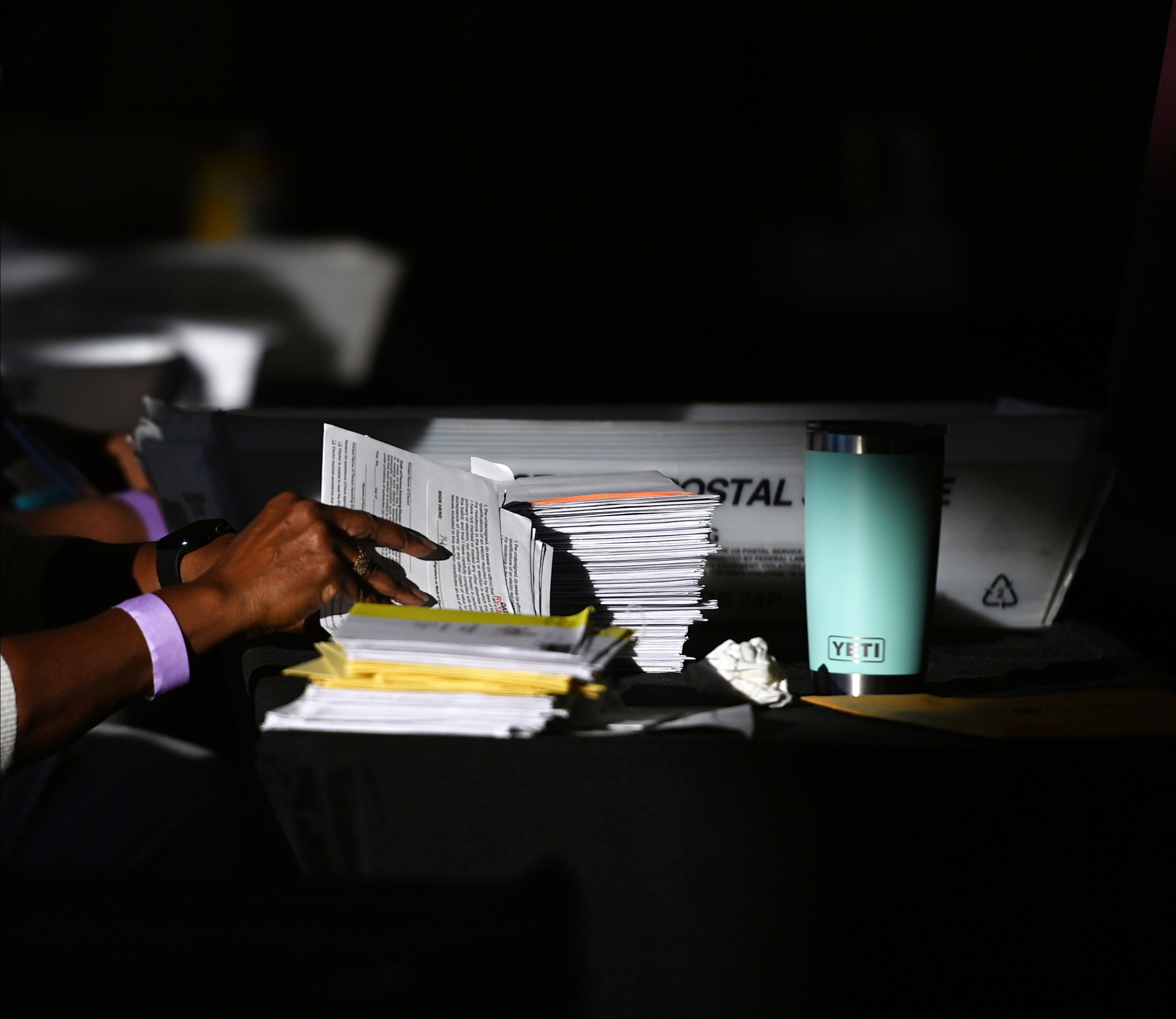 An employee of the Fulton County Board of Registration and Elections processes ballots in Atlanta, Georgia U.S., November 5, 2020. REUTERS/Brandon Bell