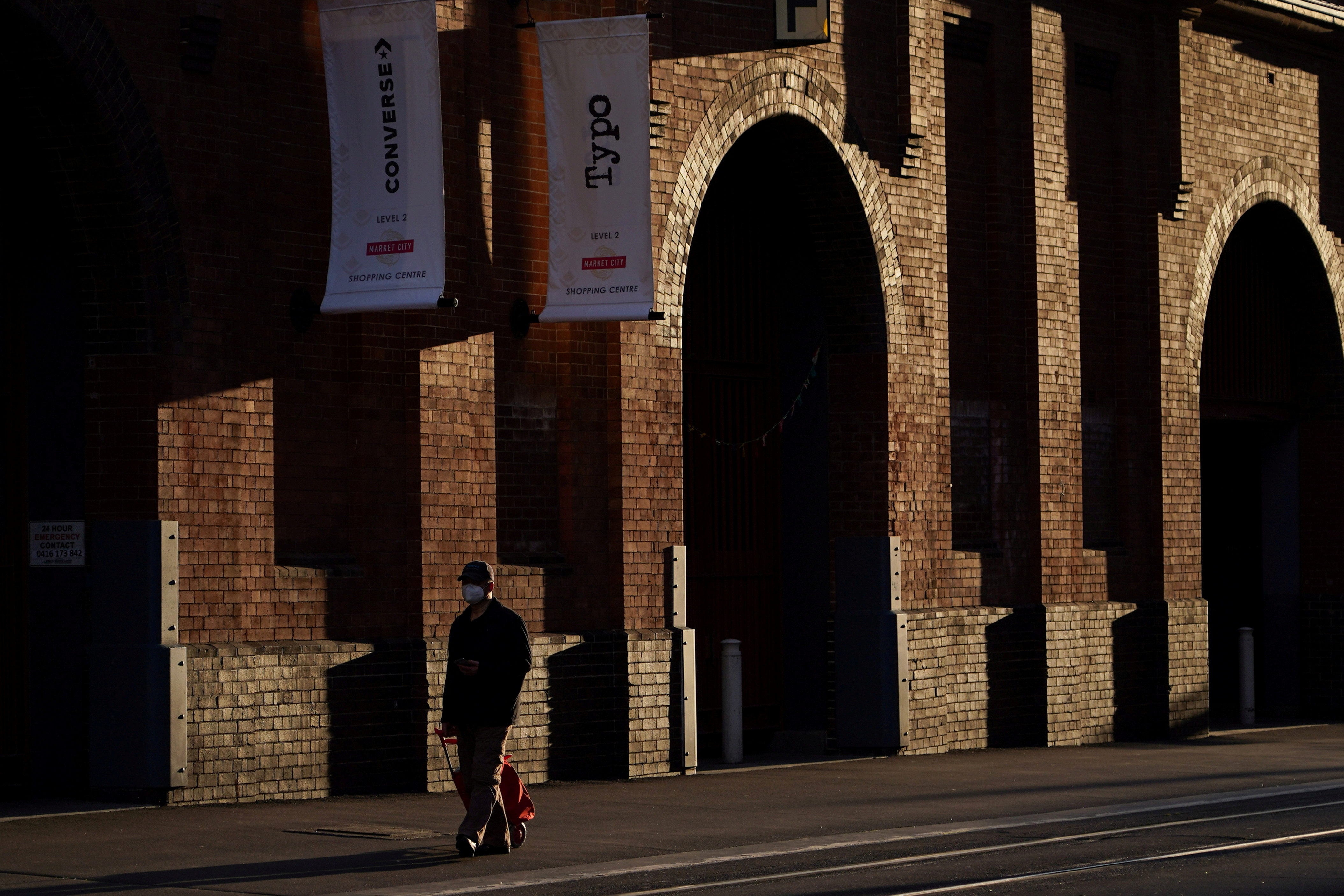 A man wearing a protective face mask walks past a usually busy market in the city centre during a lockdown to curb the spread of a coronavirus disease (COVID-19) outbreak in Sydney, Australia, August 31, 2021. REUTERS/Loren Elliott/File Photo