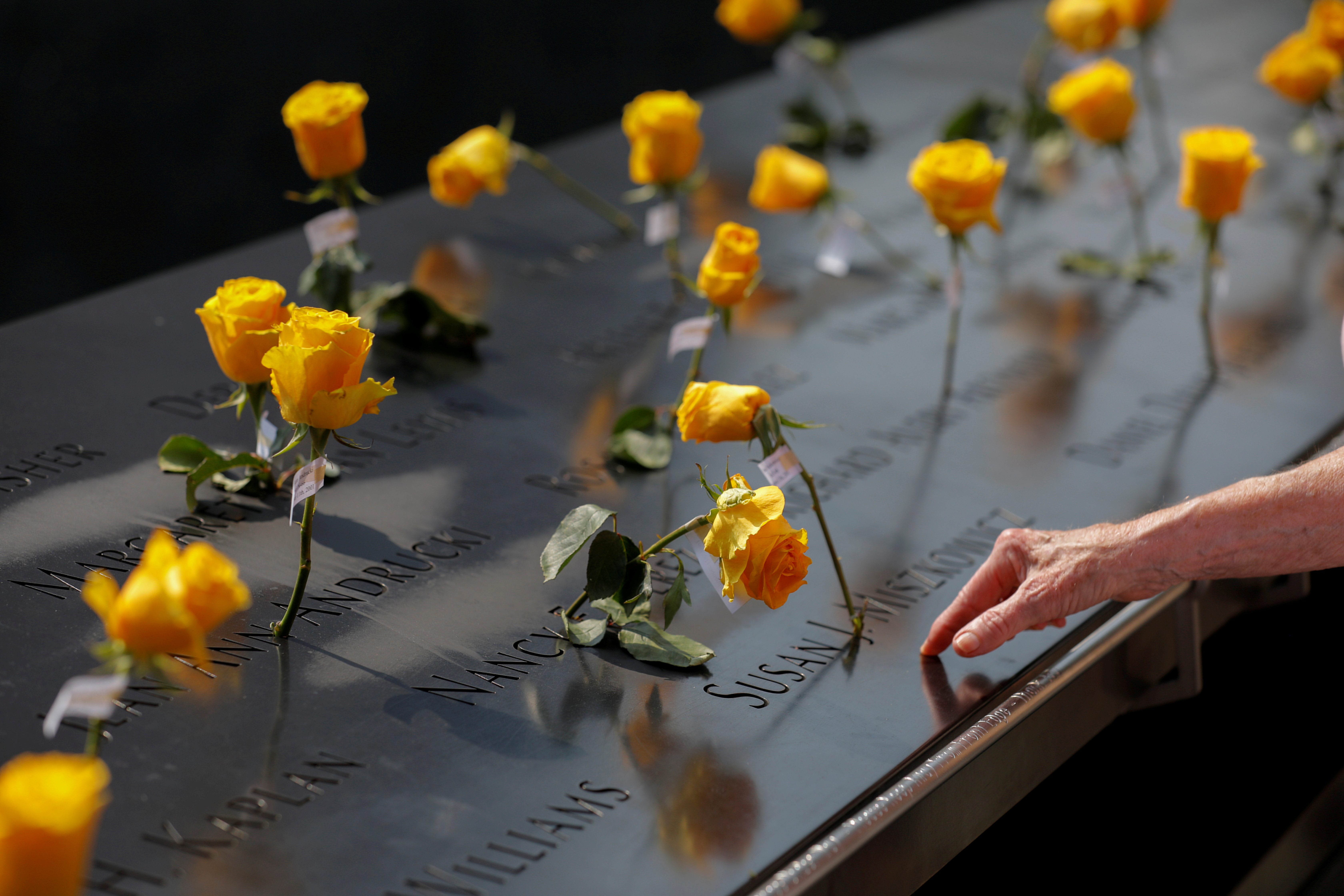 Flowers are seen in the names of victims at the National September 11 Memorial & Museum a month before the 20th anniversary of the September 11 attacks in Manhattan, New York City, U.S., August 11, 2021. REUTERS/Andrew Kelly