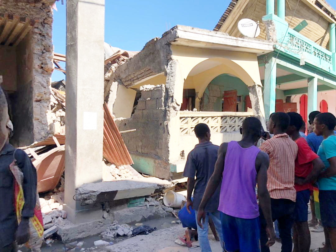 People stand in front of collapsed buildings following an earthquake in Jeremie, Haiti August 14, 2021, in this picture obtained from social media.  Courtesy of TWITTER @JCOMHaiti/ via REUTERS  ATTENTION EDITORS - THIS IMAGE HAS BEEN SUPPLIED BY A THIRD PARTY. MANDATORY CREDIT. MUST NOT OBSCURE LOGO