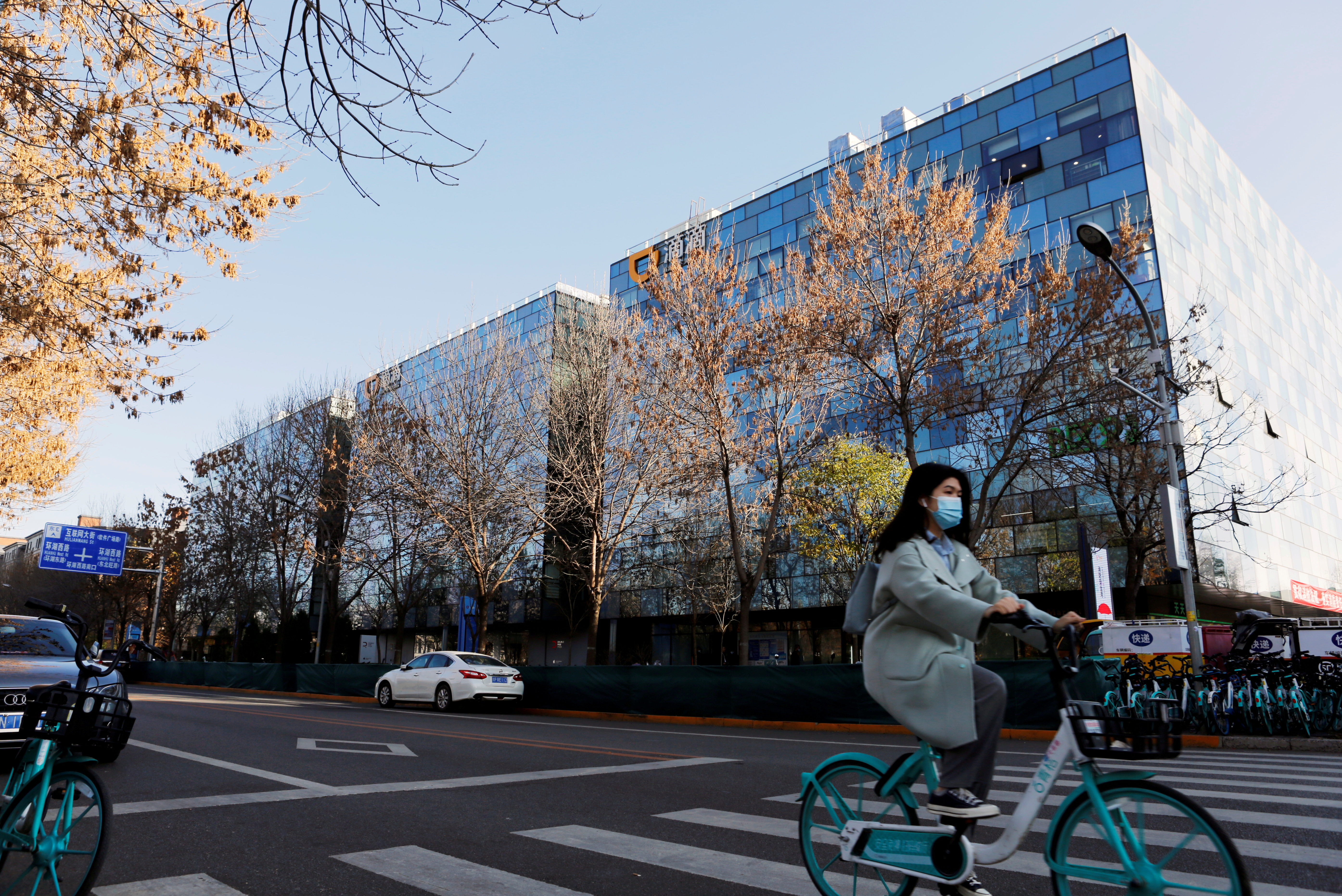 A woman rides a Didi shared bicycle past the headquarters of Didi Chuxing in Beijing, China November 20, 2020. REUTERS/Florence Lo/File Photo
