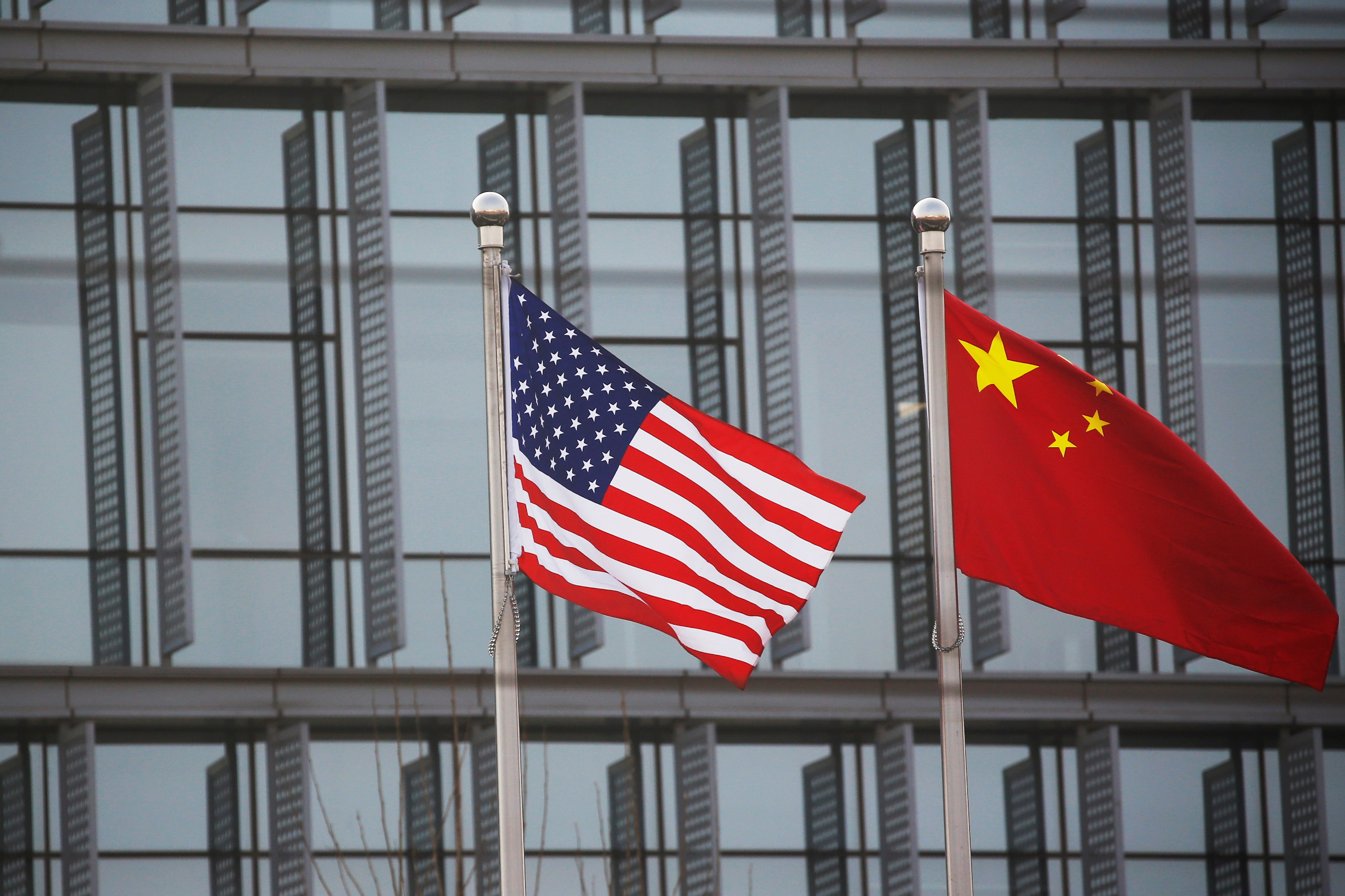 Chinese and U.S. flags flutter outside the building of an American company in Beijing, China, January 21, 2021. REUTERS/Tingshu Wang
