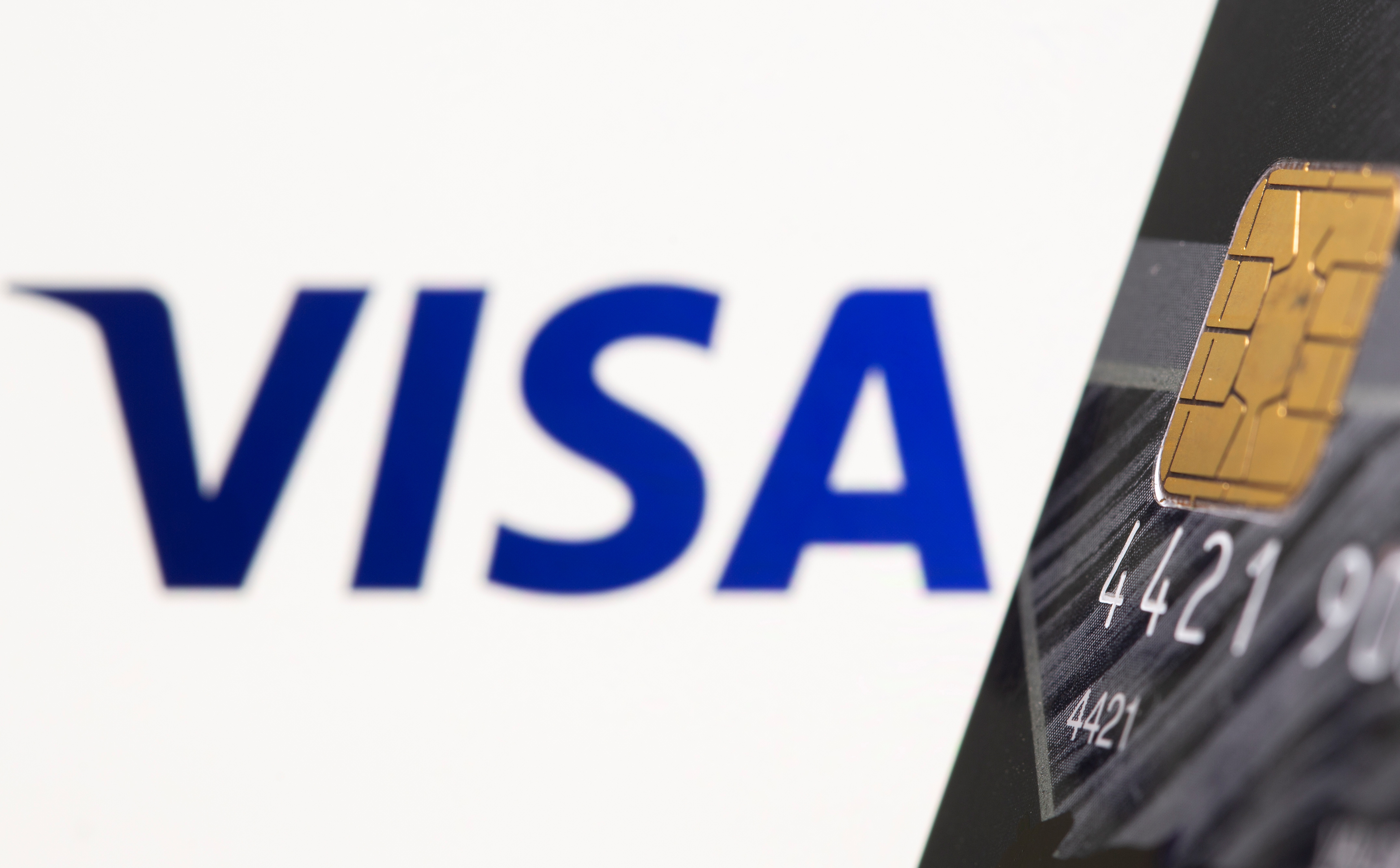Credit card is seen in front of displayed Visa logo in this illustration taken, July 15, 2021.