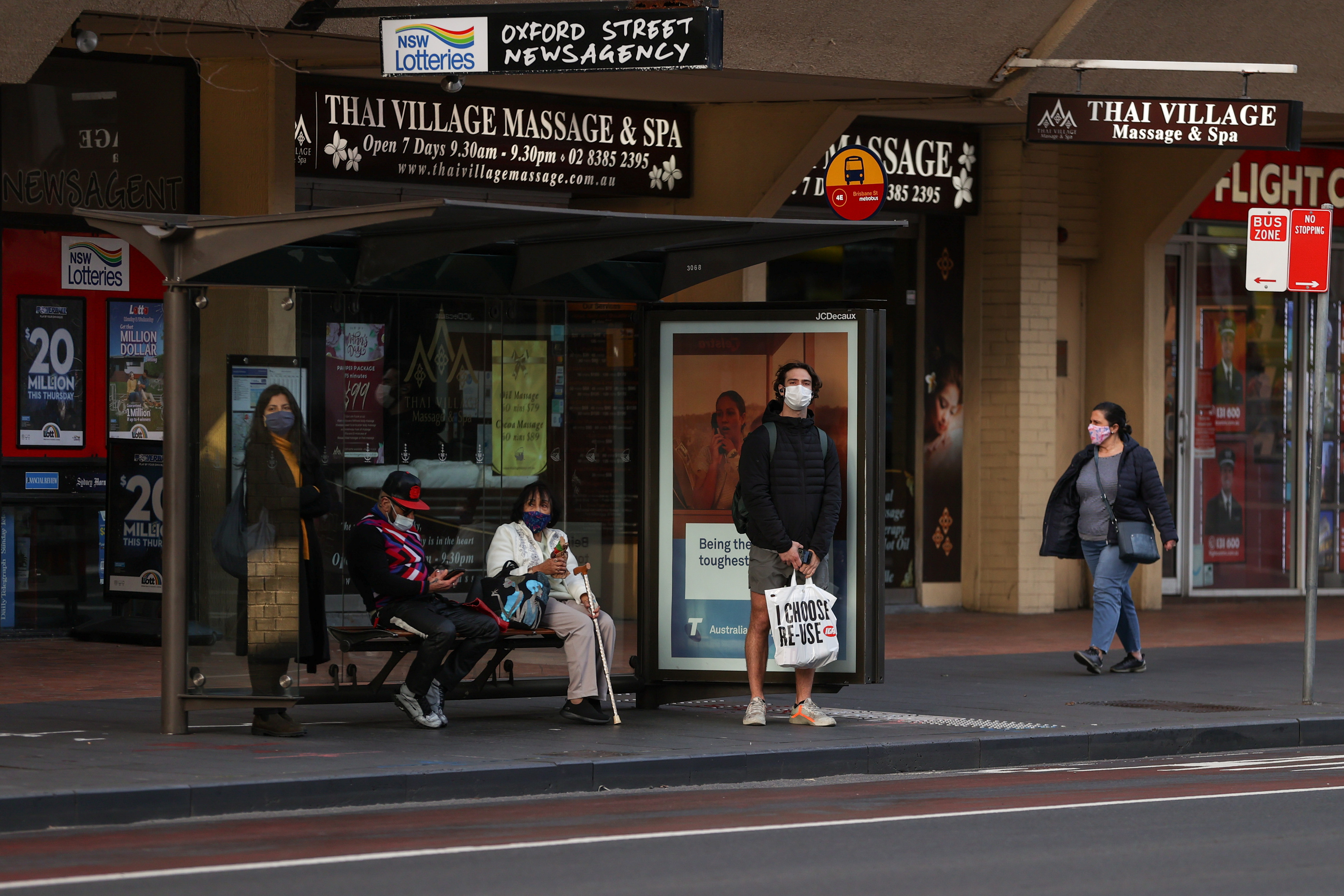 People wearing protective face masks wait at a bus stop during a lockdown to curb the spread of a coronavirus disease (COVID-19) outbreak in Sydney, Australia, July 22, 2021.  REUTERS/Loren Elliott