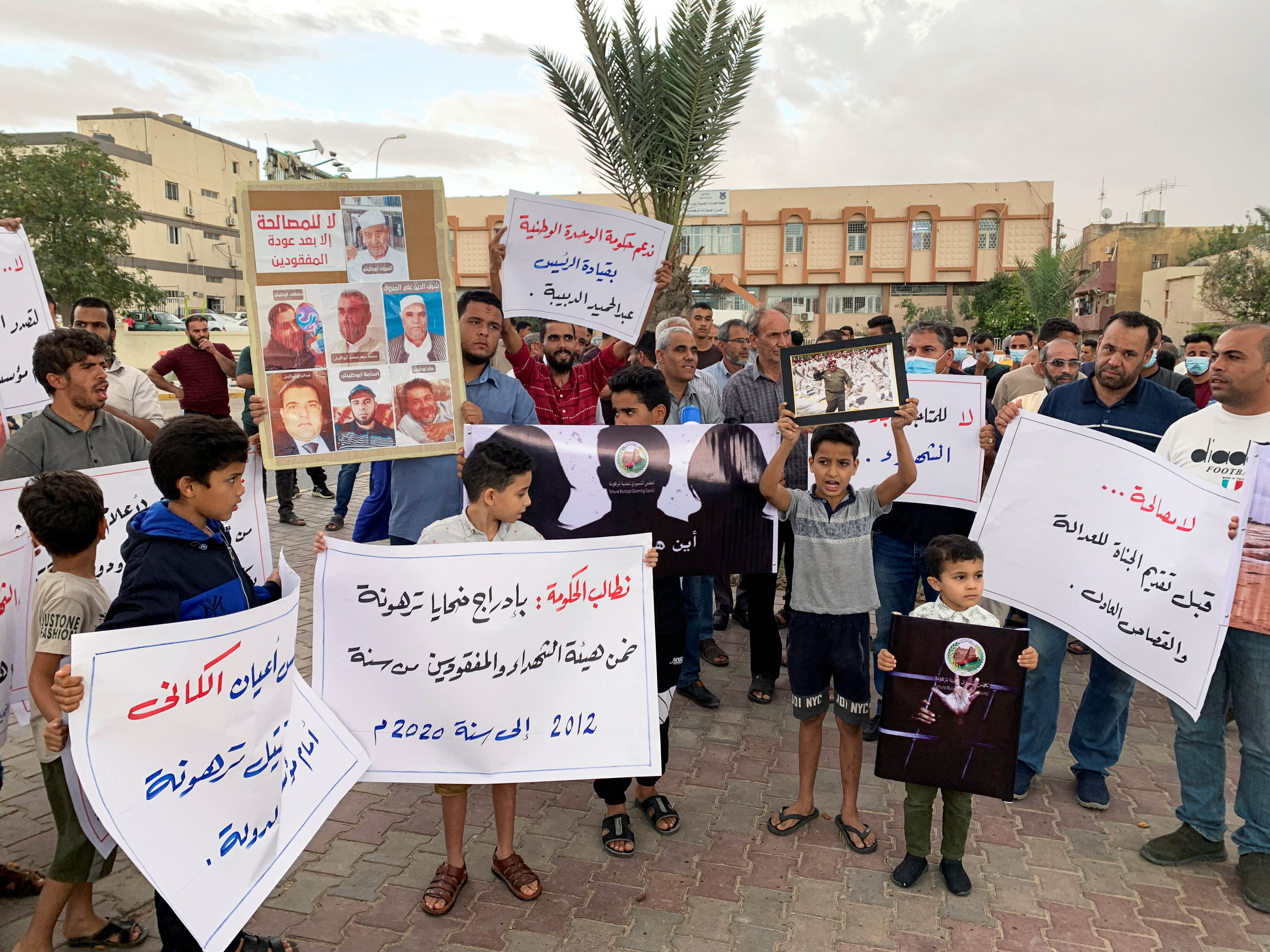 Families of victims hold signs as they demand justice for their missing ones and mass graves, in Tarhouna, Libya, Oct. 9, 2021.   REUTERS/Ayman Al-Sahili