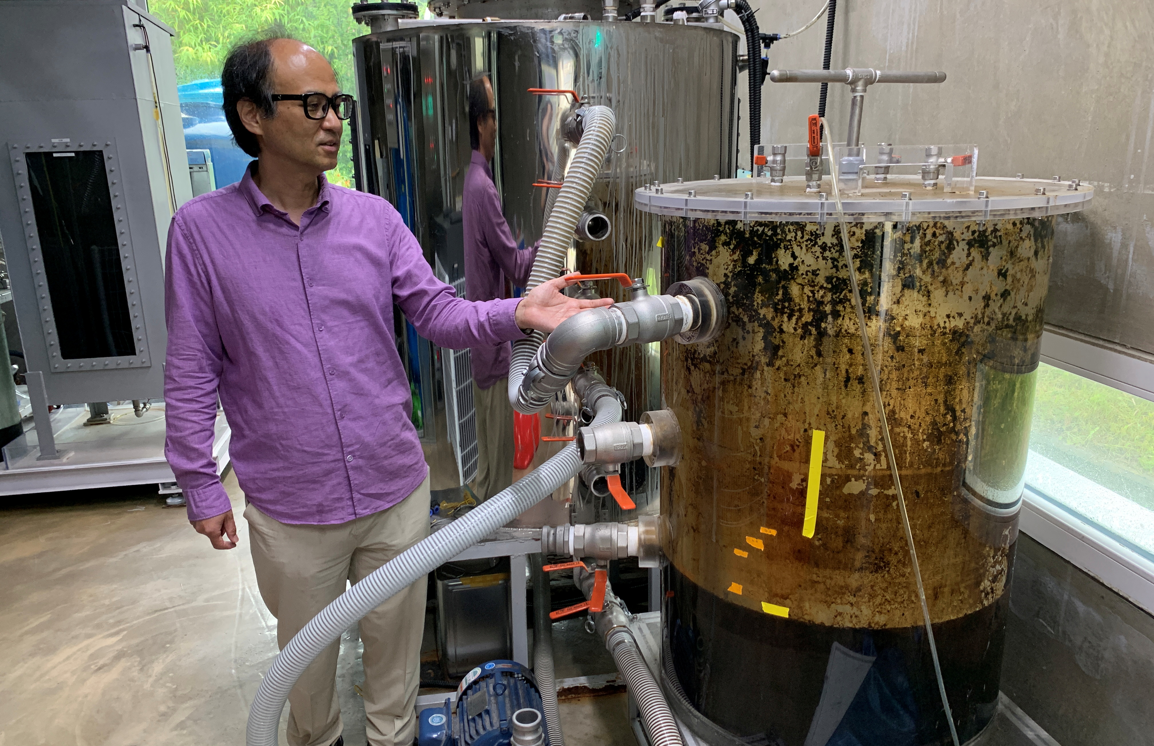 Cho Jae-weon, a South Korean professor at Ulsan National Institute of Science and Technology (UNIST), stands next to a faeces tank at a laboratory in Ulsan, South Korea, July 6, 2021. Picture taken on July 6, 2021. REUTERS/Minwoo Park