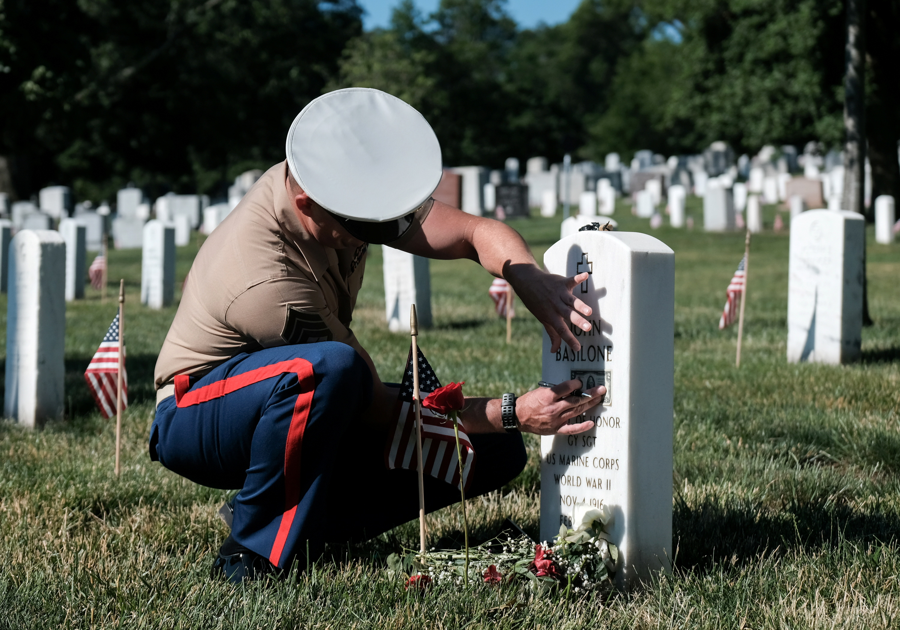 A Marine pays respect to a service member during Memorial Day in honor of those lost in war at Arlington National Cemetery across the river from Washington in Arlington, Virginia, U.S., May 31, 2021.  REUTERS/Michael A. McCoy