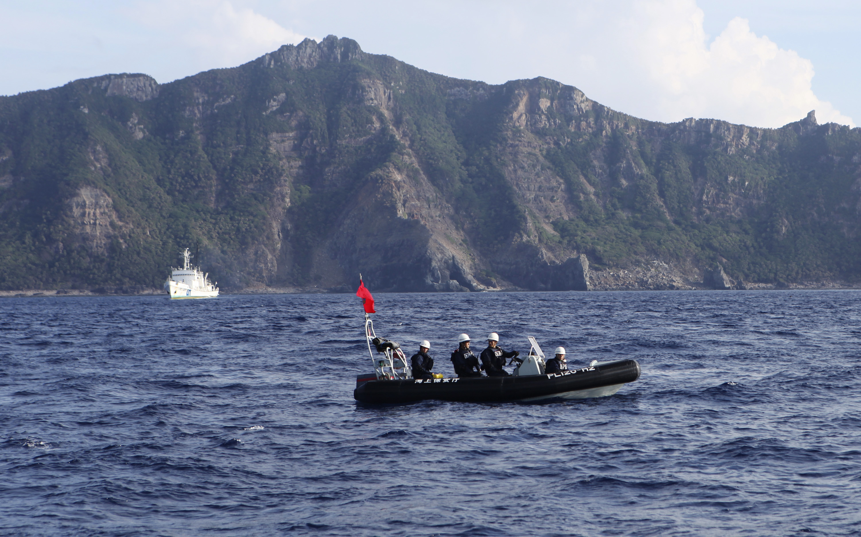 A Japan Coast Guard boat (front) and vessel sail as Uotsuri island, one of the disputed islands, called Senkaku in Japan and Diaoyu in China, is pictured in the background, in the East China Sea August 18, 2013. REUTERS/Ruairidh Villar